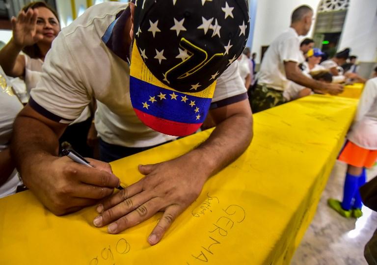 Un ciudadano venezolano firma la bandera de su país en una jornada de compatriotas reunidos en Curazao.