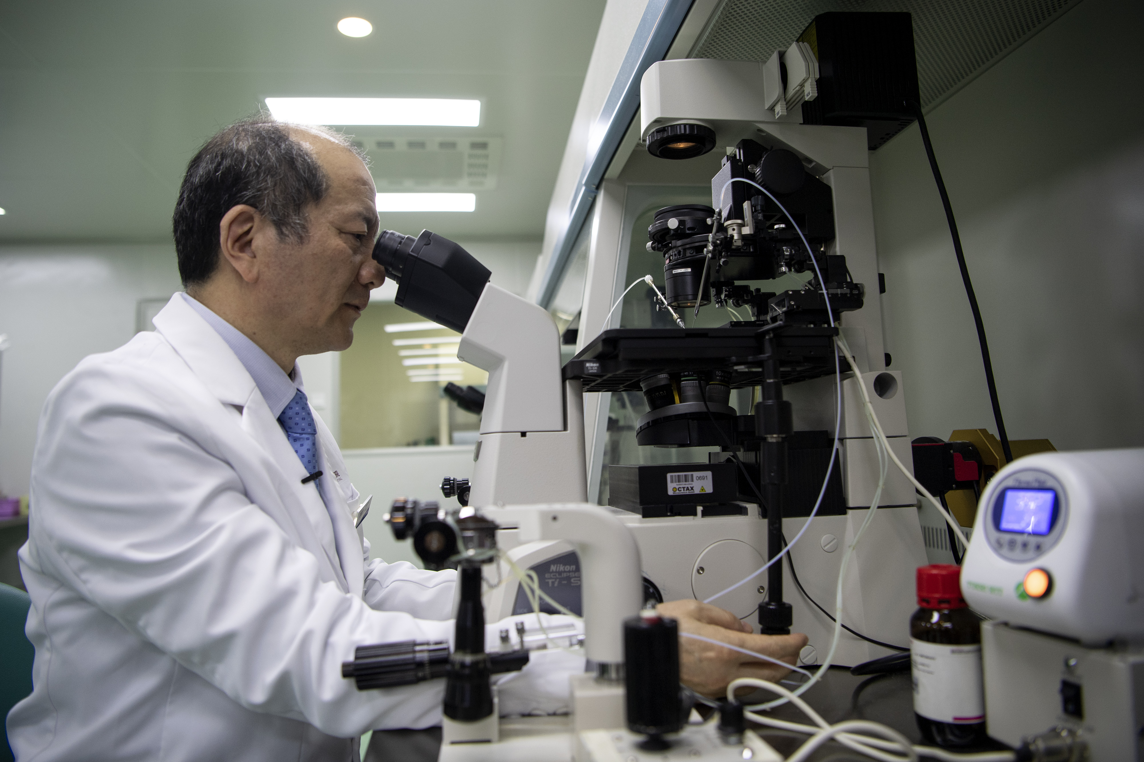 El doctor Liu Jiaen, director de un hospital de fertilidad, mira una muestra de esperma a través de un microscopio en el hospital de Beijing.