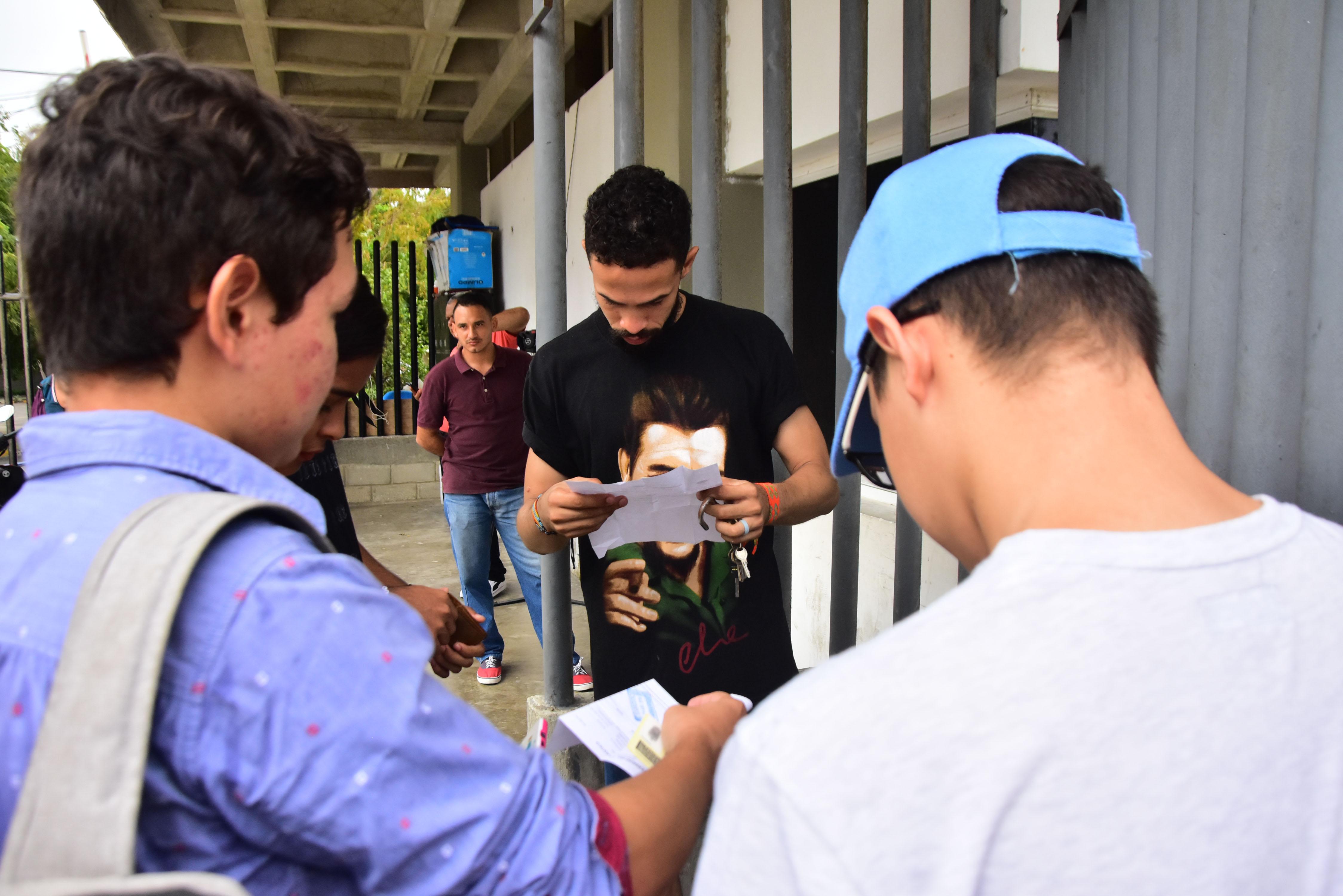 Un joven verifica los documentos de un grupo de estudiantes de Uniatlántico.