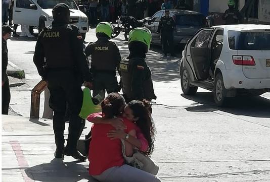 Dos mujeres lloran en la escena del crimen.