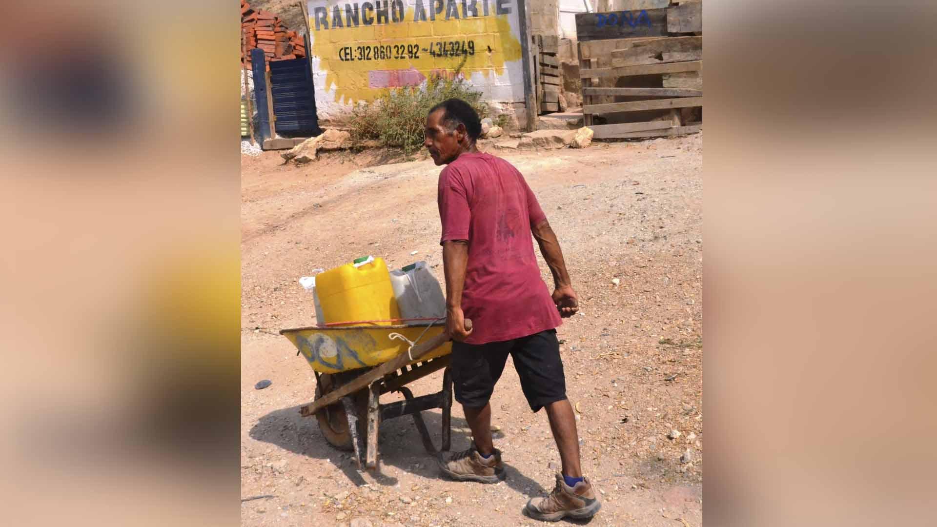 Las pimpinas y las carretillas son usadas para llevar el agua a las casas de sectores como Taganga.