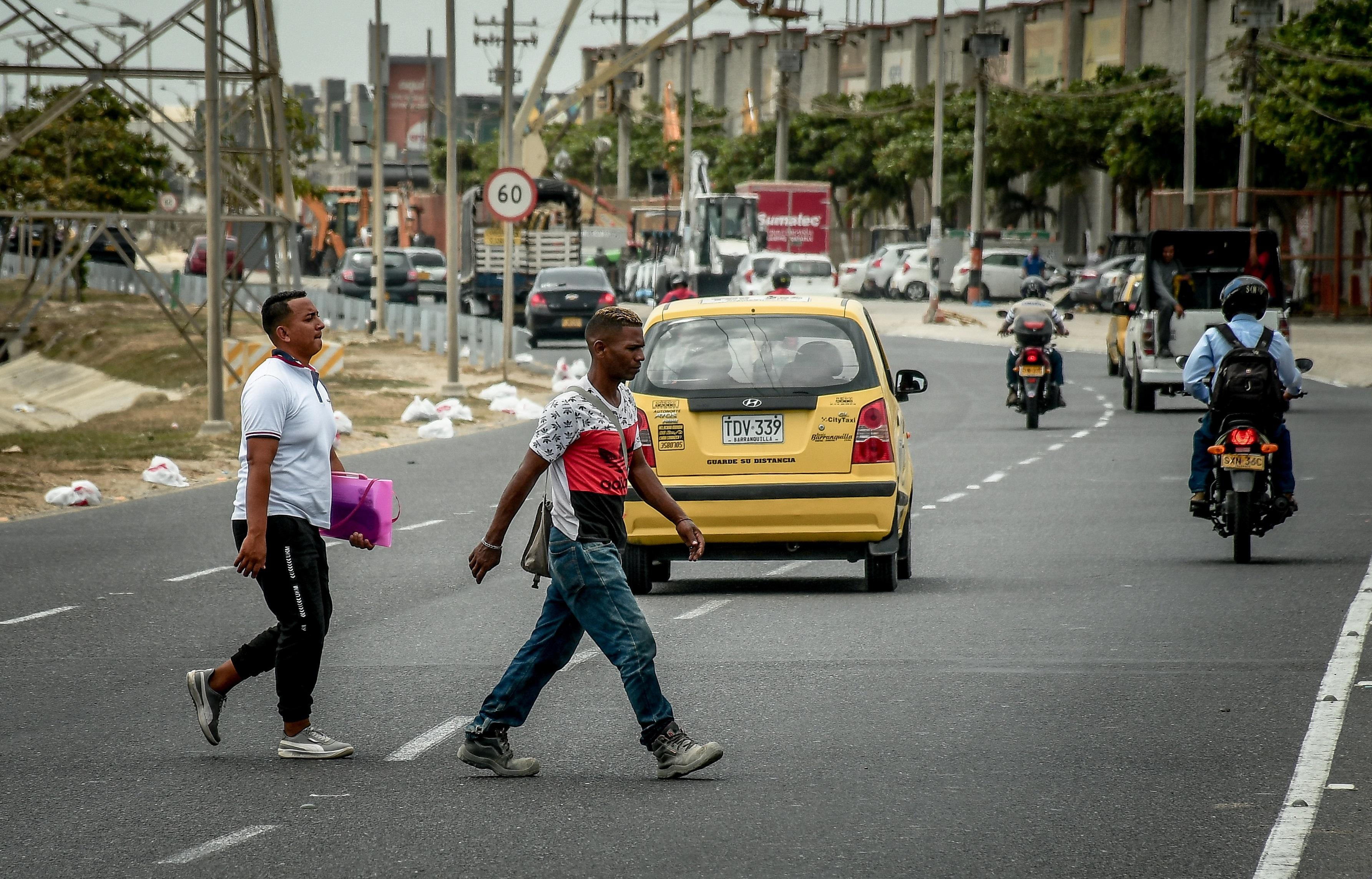 Dos peatones cruzan de prisa la Circunvalar, una vía de alto tráfico vehicular.
