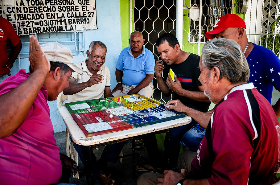 Los vecinos del barrio Las Nieves ríen y celebran en medio de un partido de parqués.