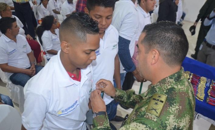 Un beneficiario recibe medalla de héroe.
