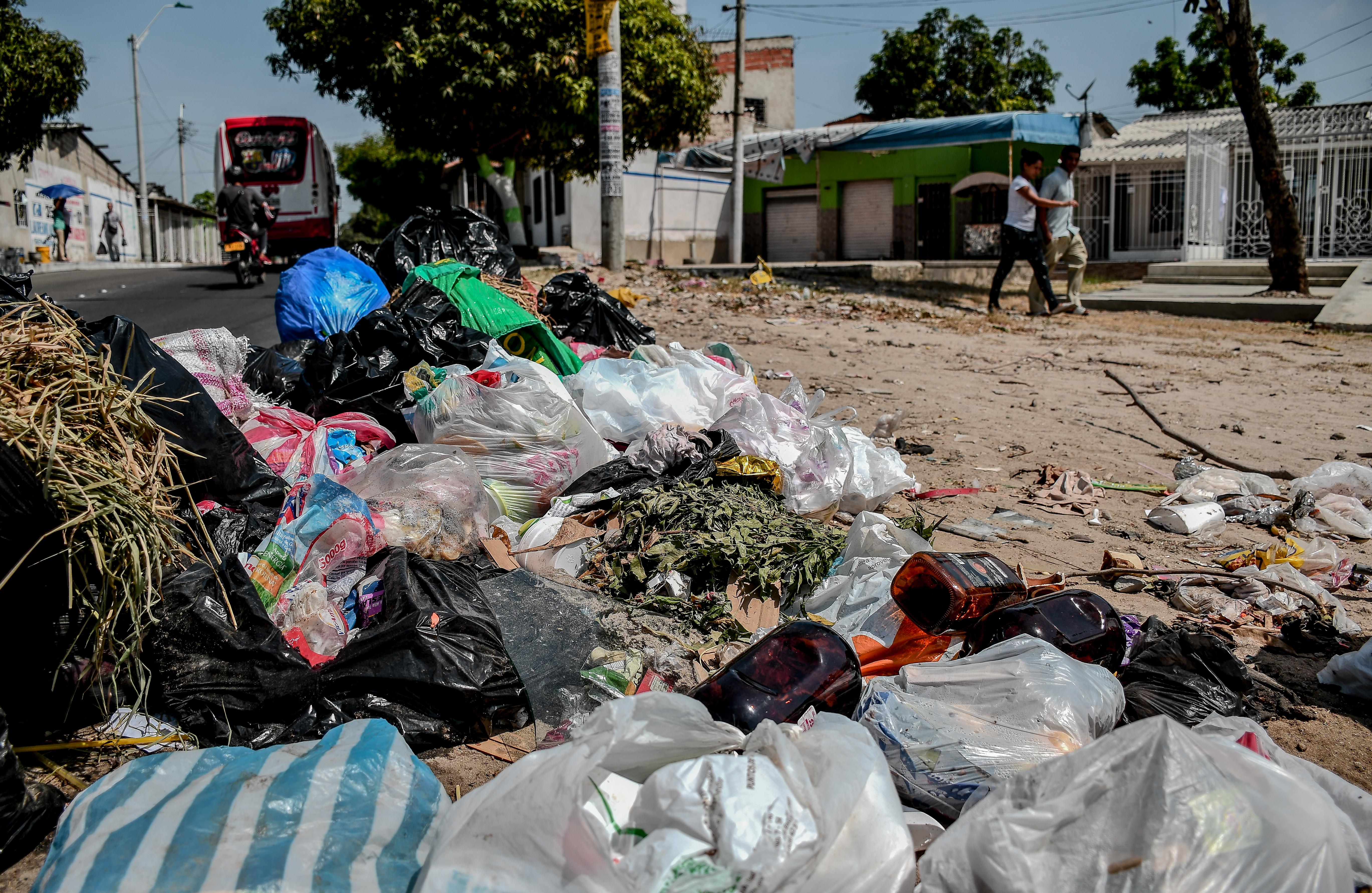 Algunas de las bolsas negras están abiertas y de su interior salen residuos que quedan en las calles.
