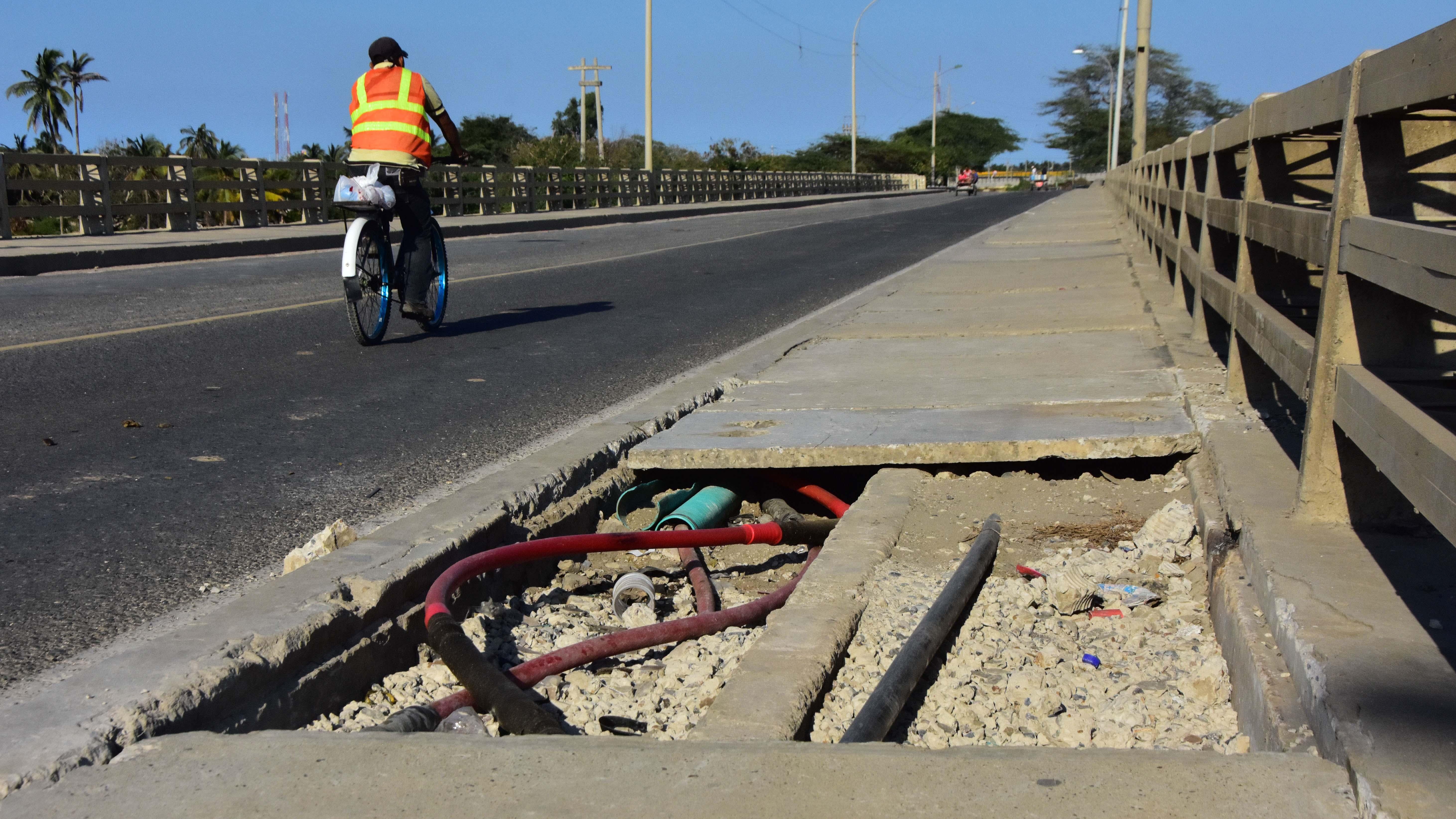 En el paso peatonal del viejo puente se observan cables y tubos a la intemperie.