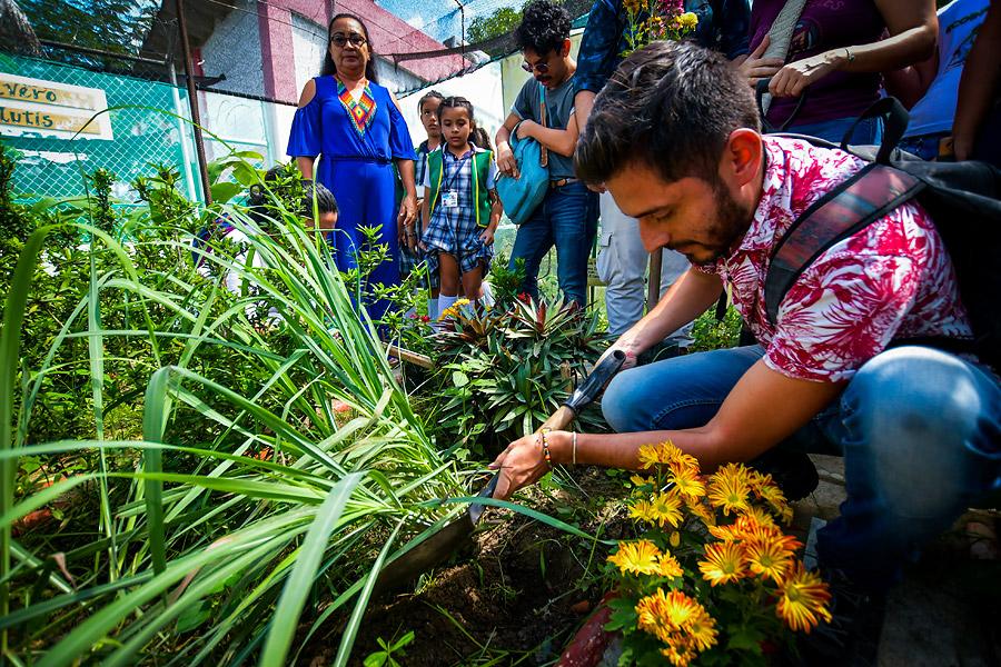 Javer Herrera siembra plantas en el mariposario.