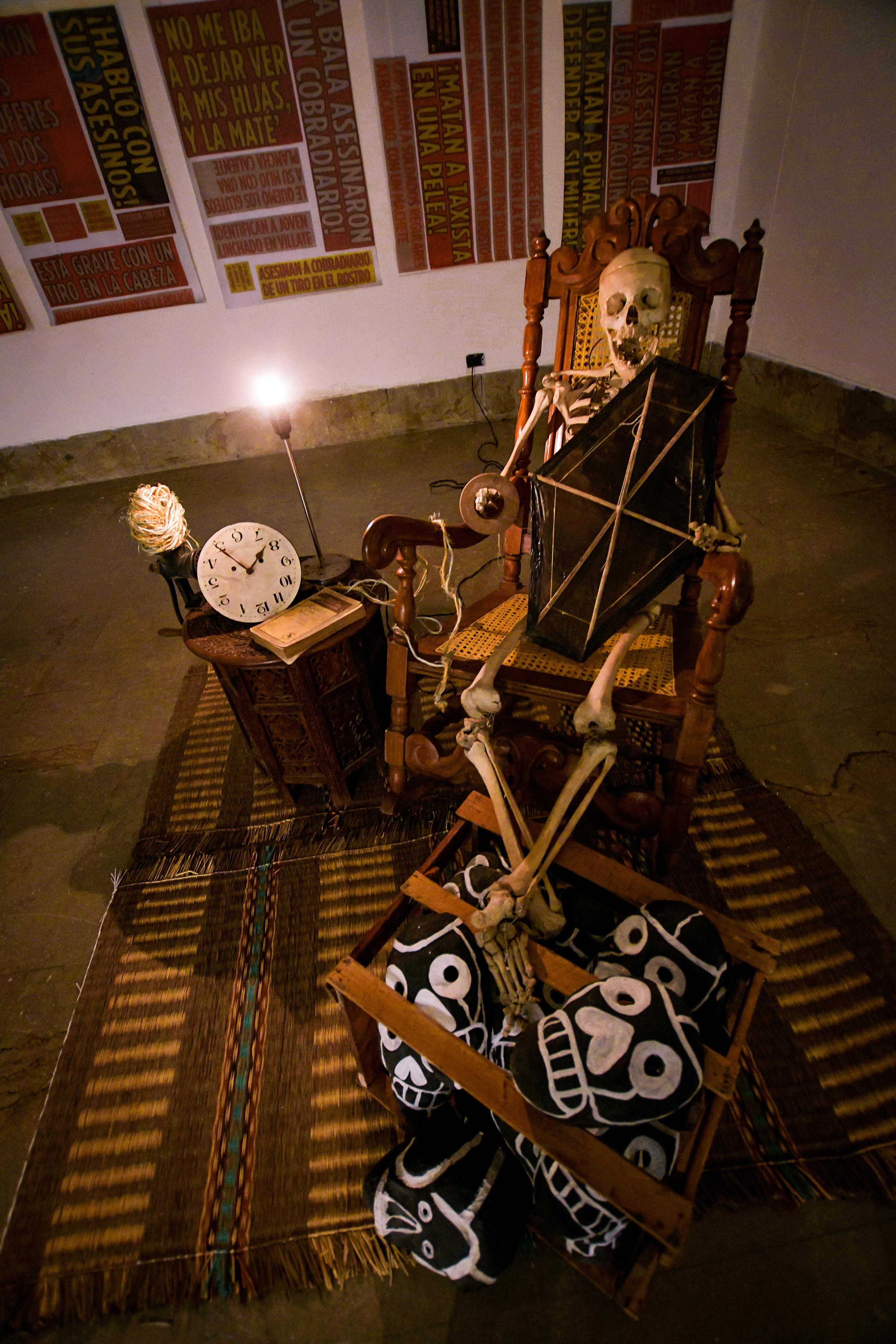 Soledad se llama la esqueleto que apoya los pies sobre un guacal lleno de máscaras de cartapesa.