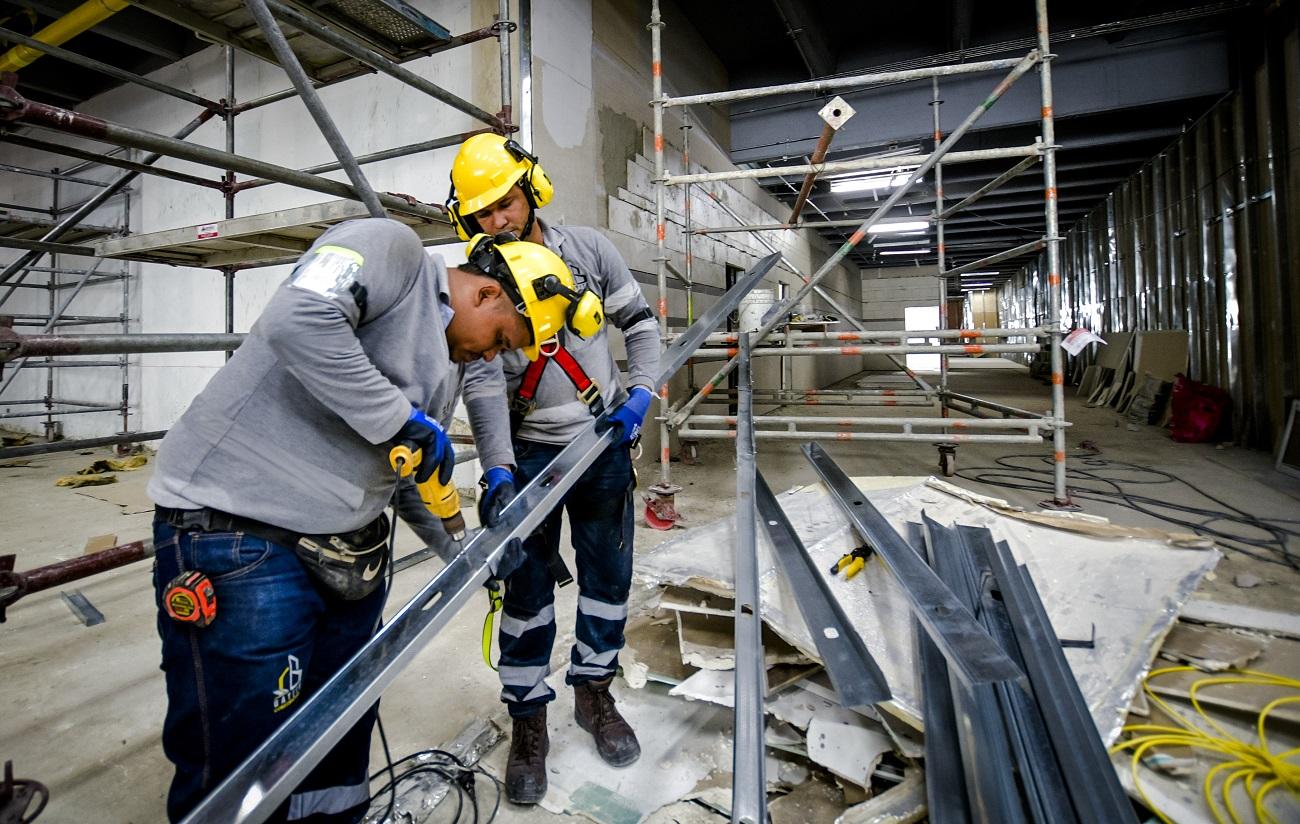 Dos trabajadores realizan labores para la construcción de módulos para el techo.