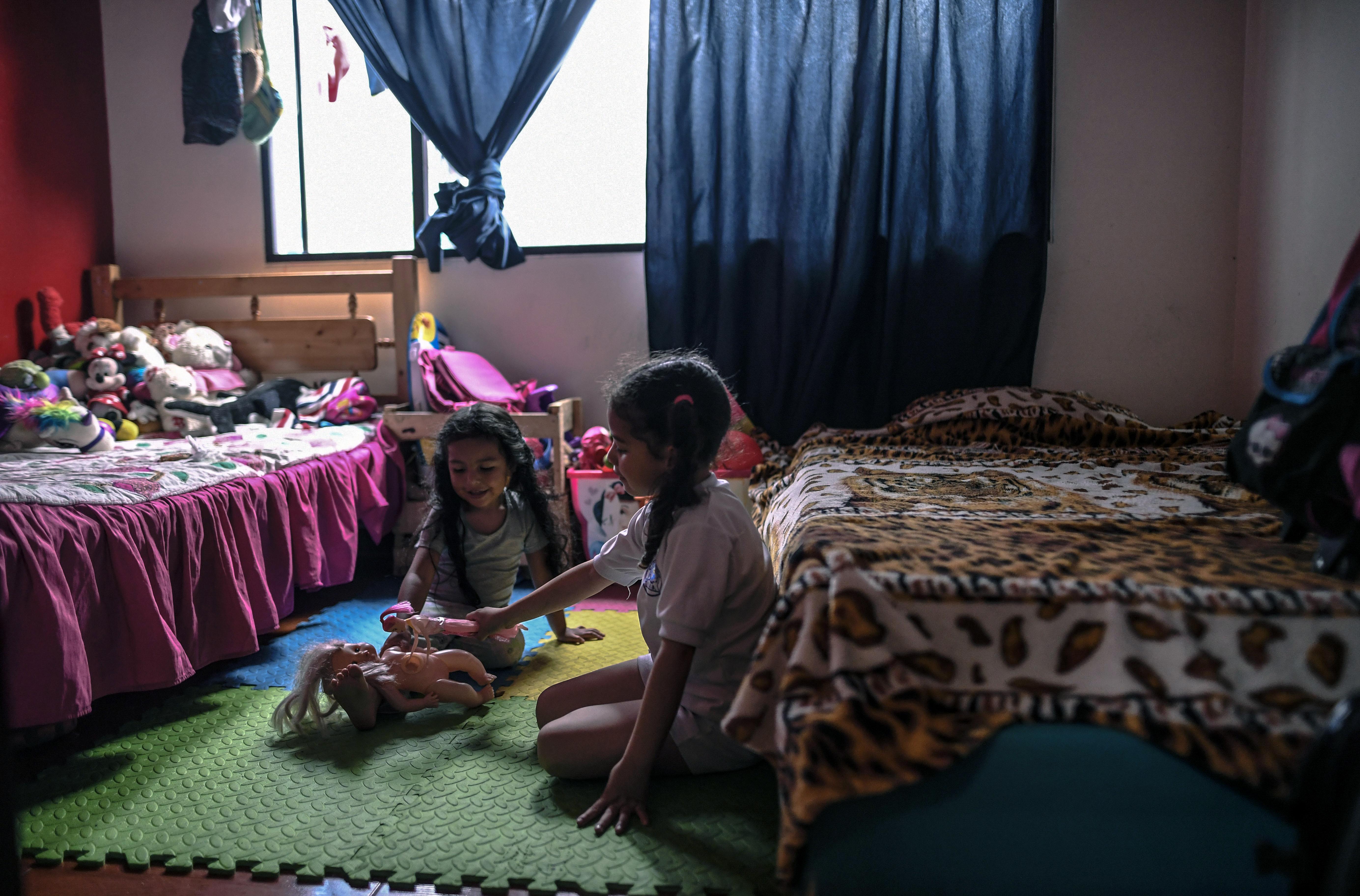 Arianna y Juliana Celis juegan en el cuarto donde viven en Bogotá. Desde 2014 se han mudado 7 veces.