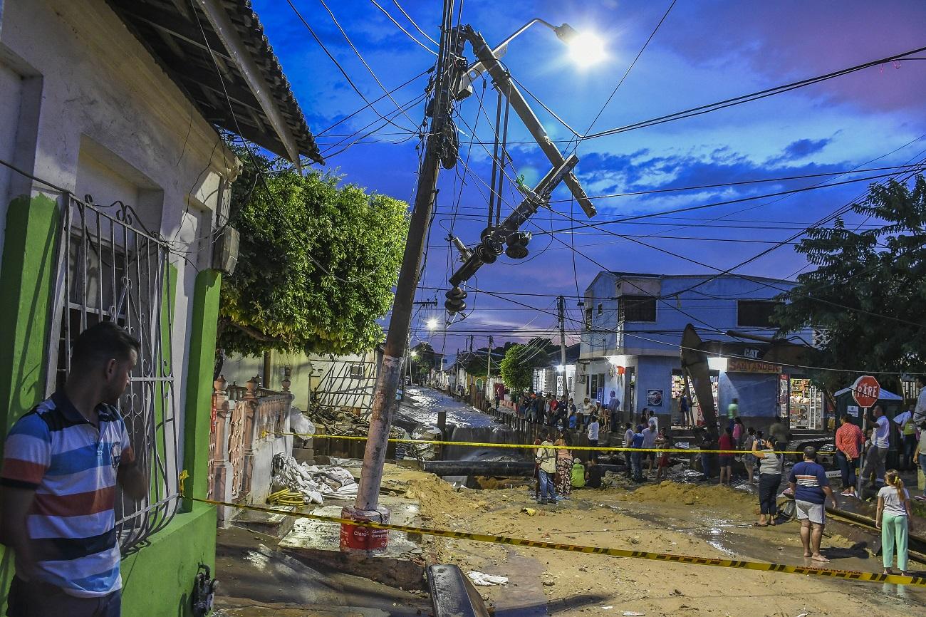 Varios habitantes observan un poste que está a punto de colapsar en el barrio Chiquinquirá.