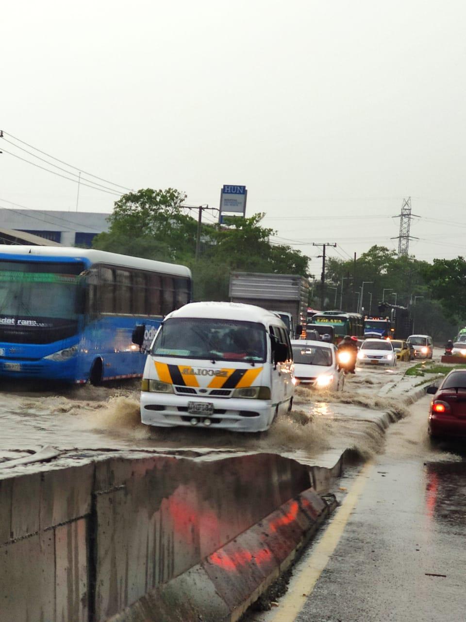 Vario vehículos pasan por la calle 30 con carrera 2, donde un arroyo se desbordó.