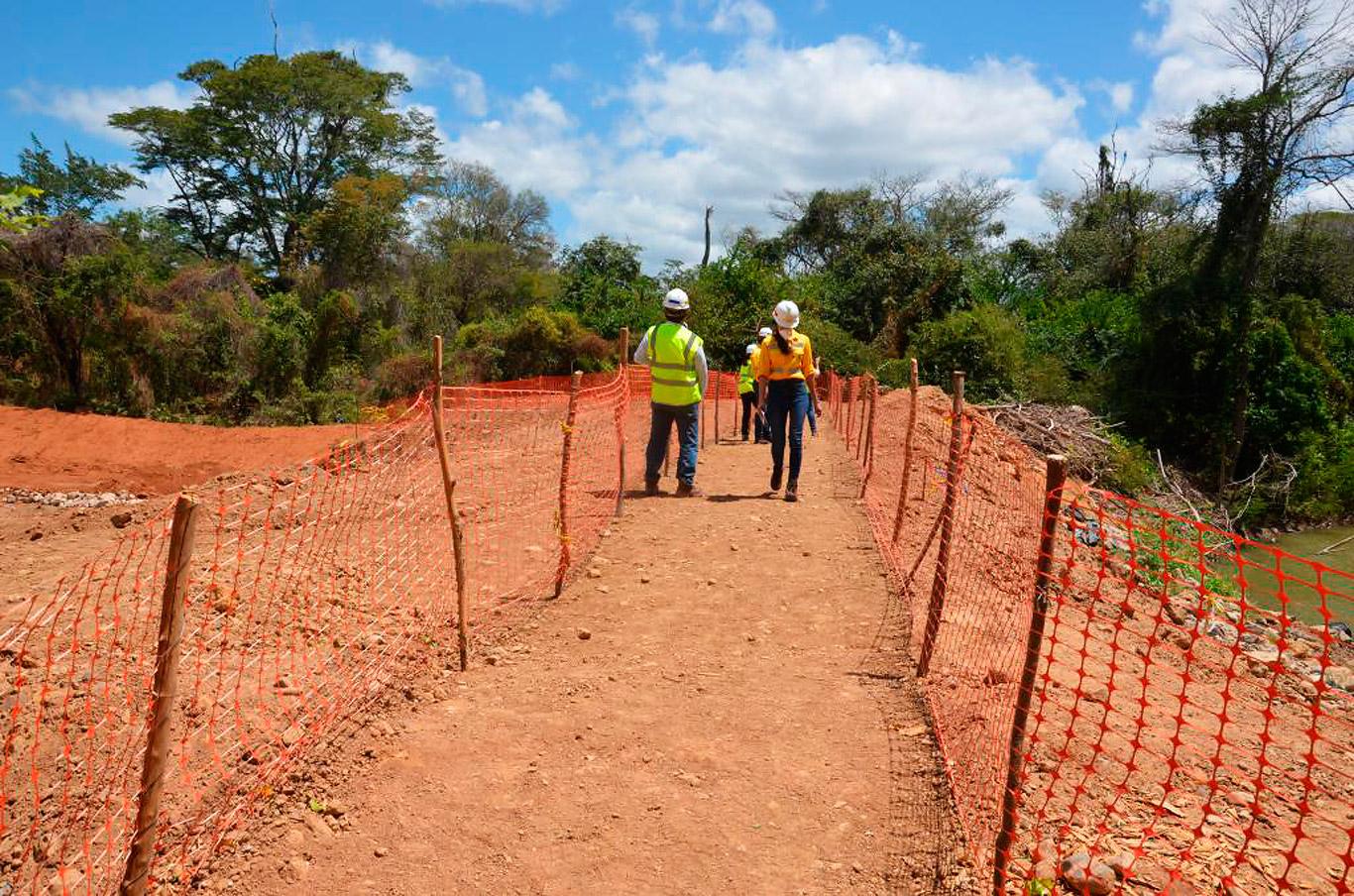 Un grupo de trabajadores e ingenieros caminan por el lado nuevo del cauce del arroyo Bruno; al otro lado se aprecia el viejo caudal.
