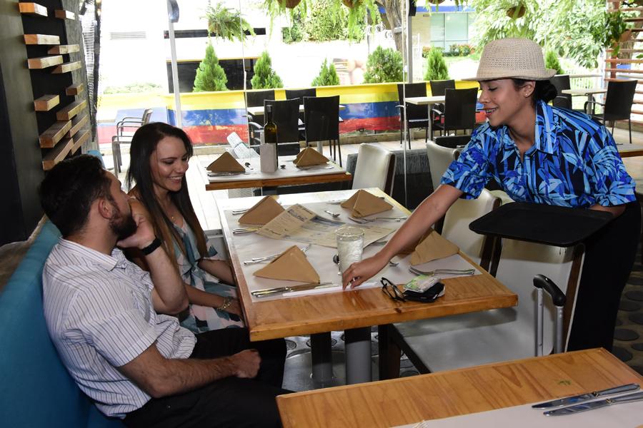 Lorayne Solano atiende a una pareja de novios, los primeros comensales en llegar al restaurante.