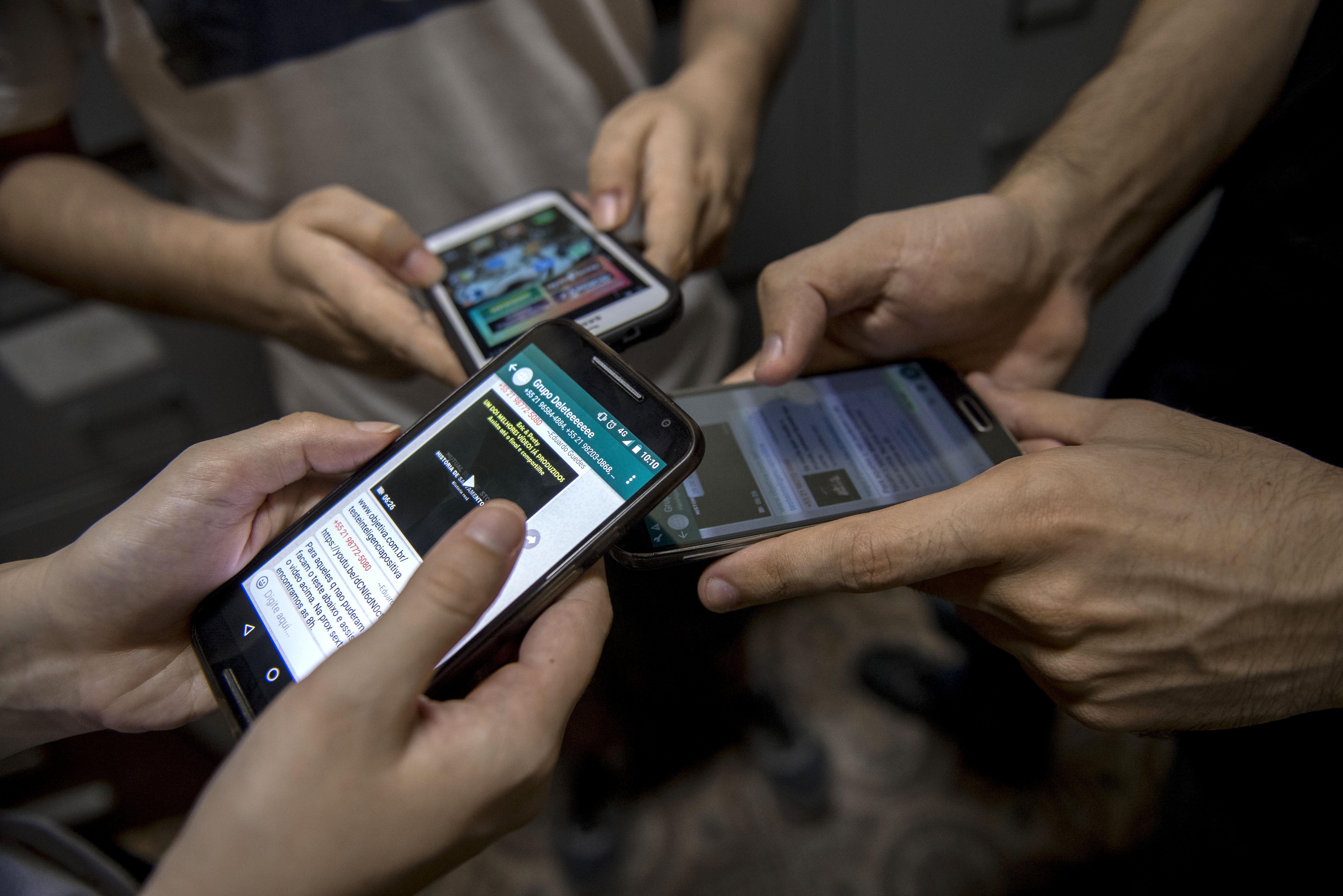 Los pacientes del grupo terapéutico en dependencia digital 'Eliminar' muestran sus teléfonos celulares dentro de una clínica en Río de Janeiro, Brasil.