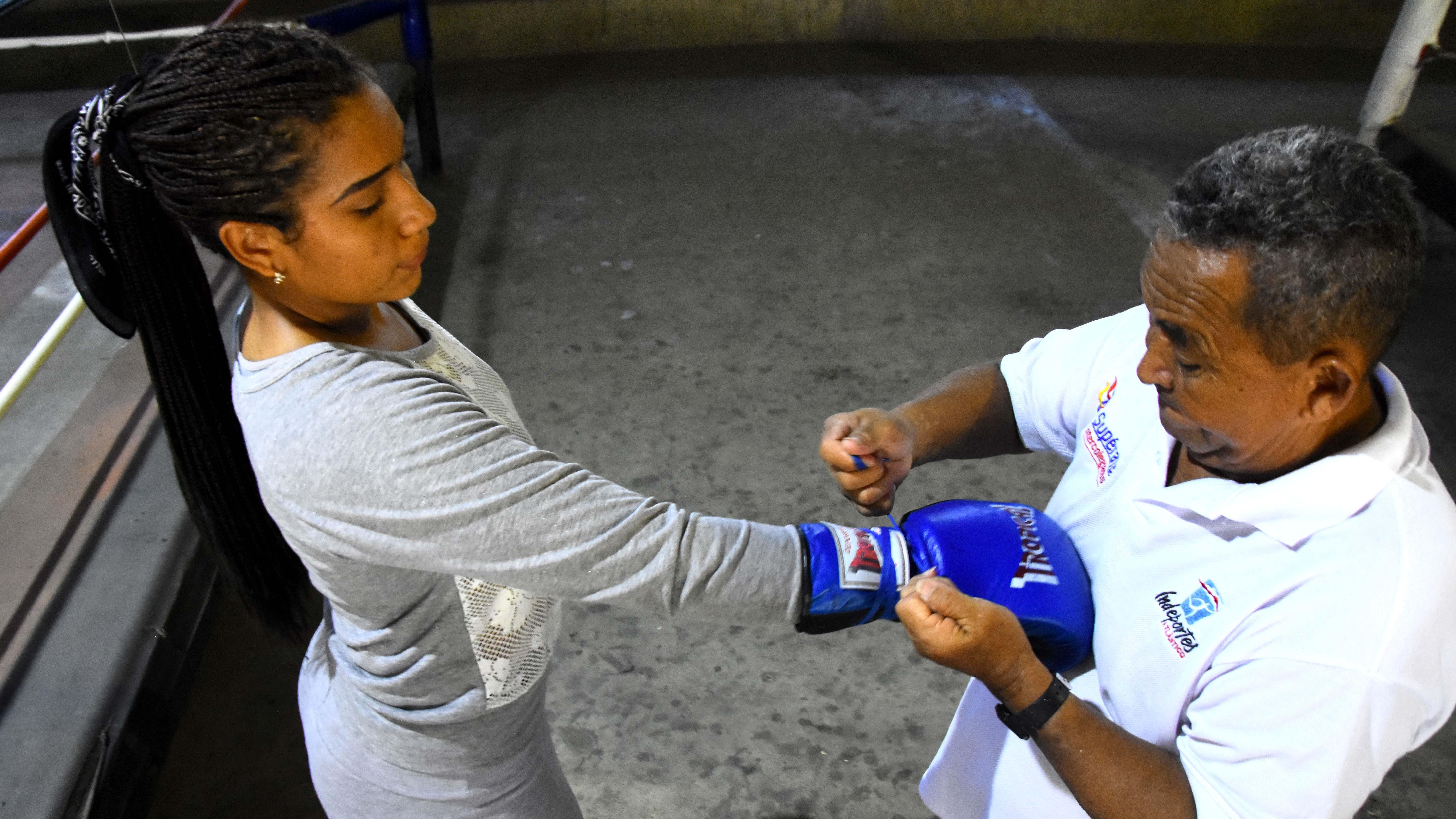 El entrenador Carlos Ramos alistando a su pupila Shirleidis Orozco para una nueva sesión de guanteo.
