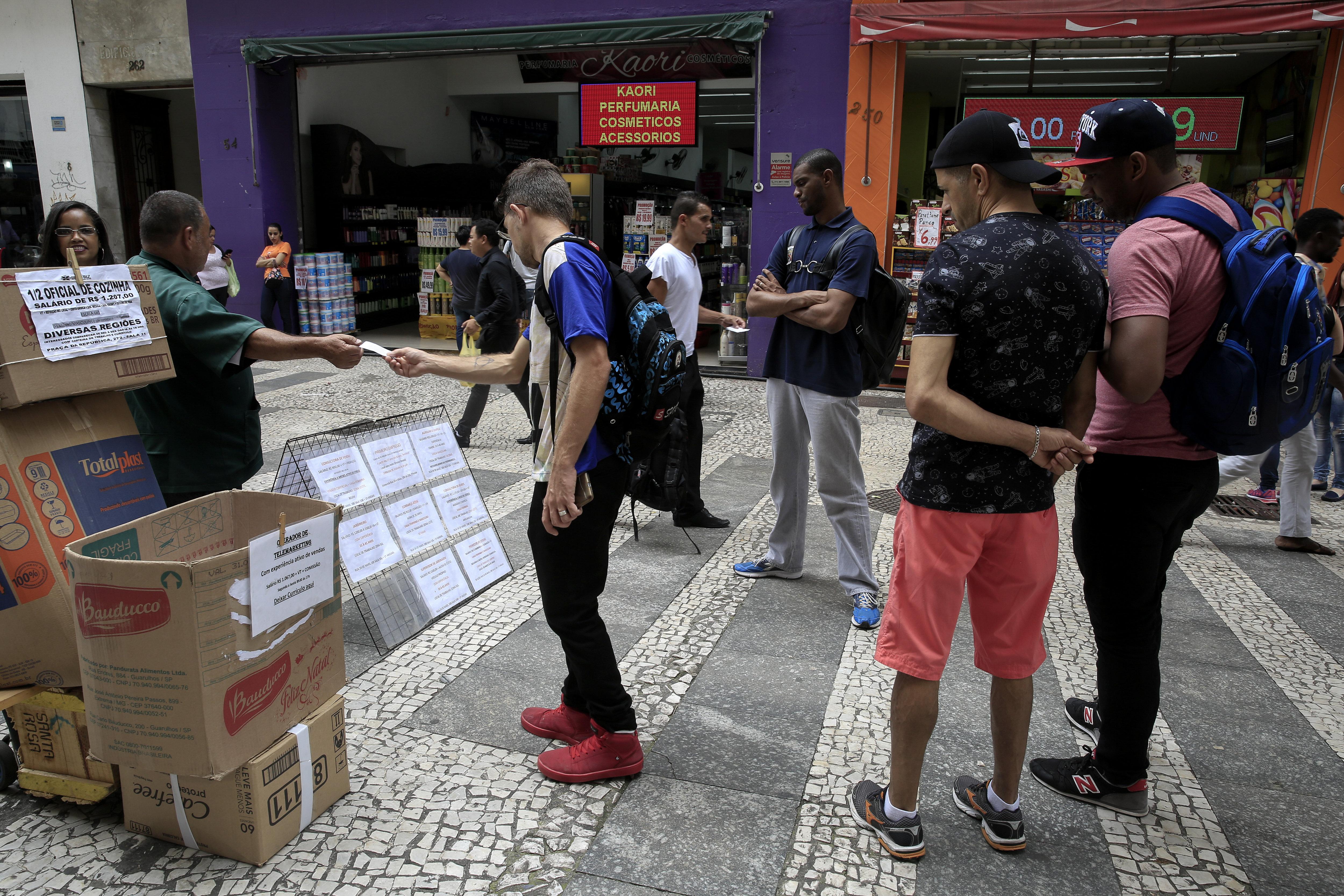 Personas se interesan en ofertas de empleo en un centro comercial en Sao Paulo.