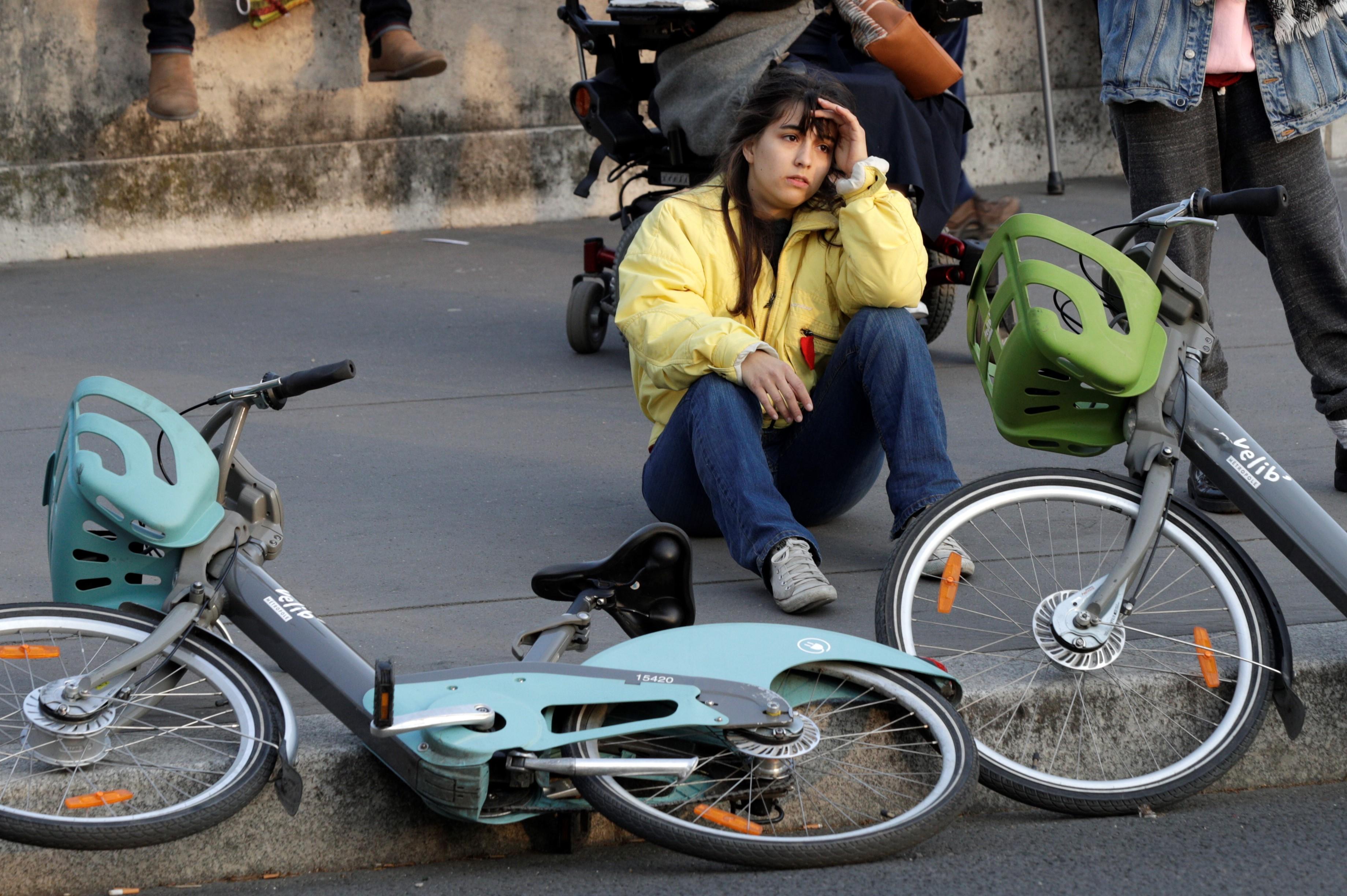 En medio de la ciclovia, una parisina se lamenta sobre los hechos.