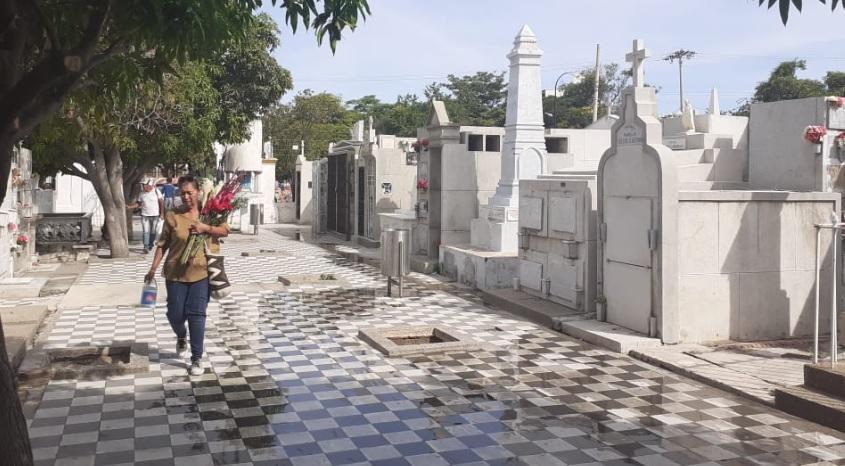 Una mujer camina con un ramo de flores en el cementerio de Santa Marta.