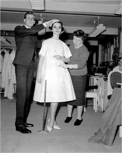 Yves Saint Laurent durante su primer desfile con Dior al lado del vestido trapecio, símbolo de la época.