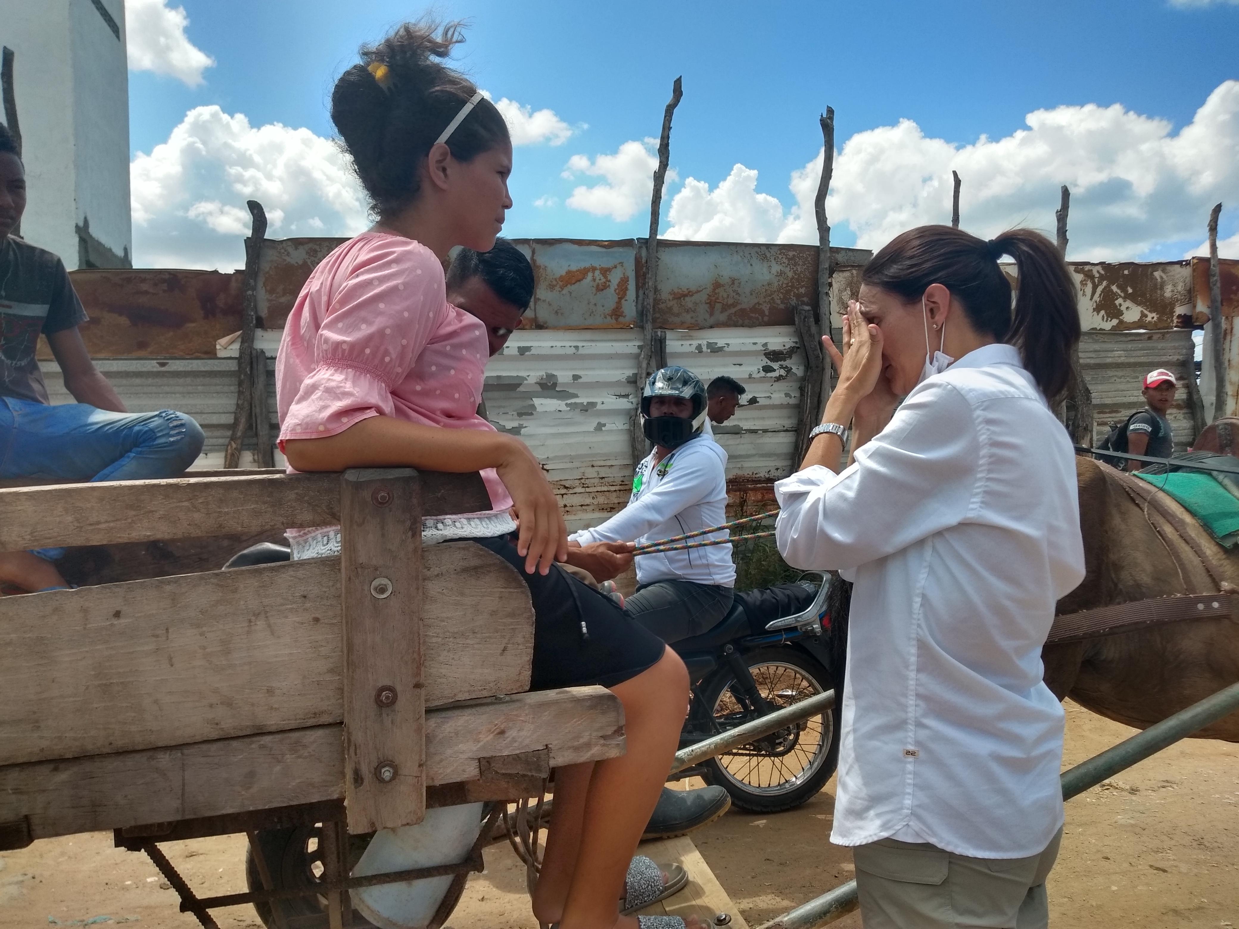 Juliana Pungiluppi se protege el rostro del sol mientras habla con una madre de familia del sector aledaño al mercado nuevo de Riohacha.