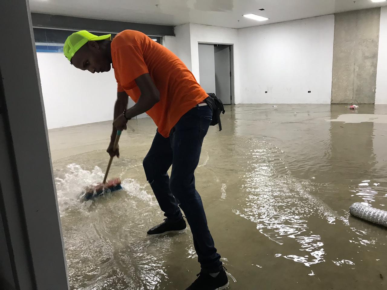 Operarios del estadio tratando de sacar el agua con escobas.