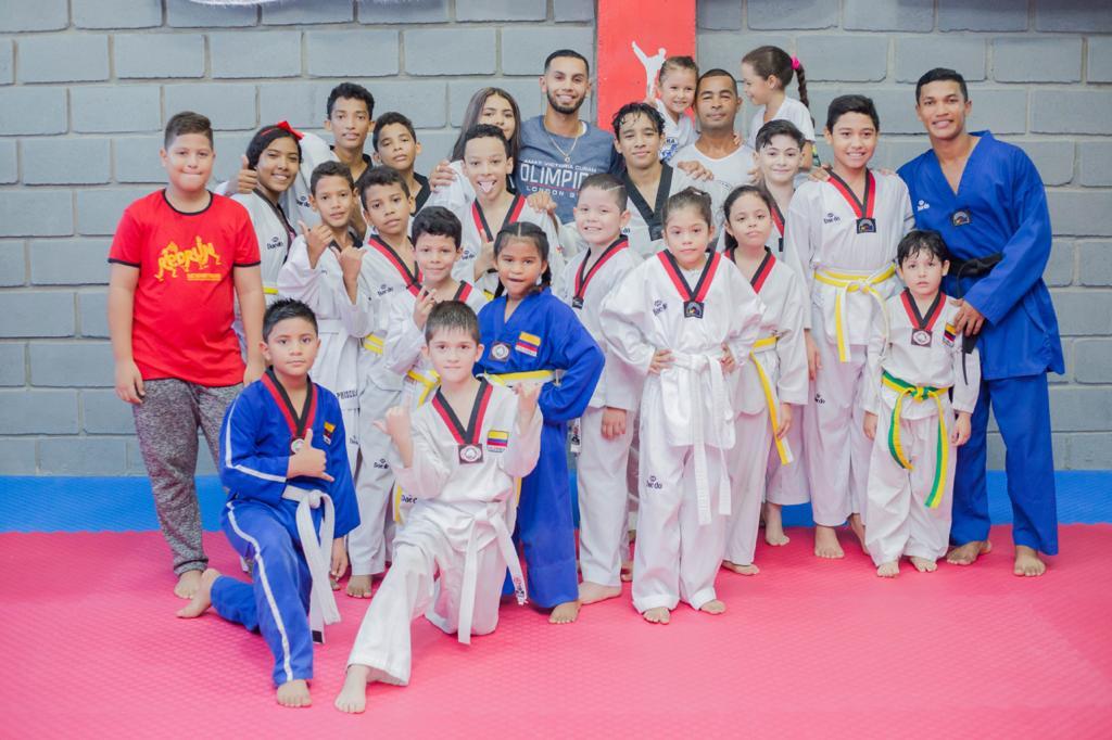 Óscar Muñoz rodeado de niños y jóvenes de su escuela de taekwondo.