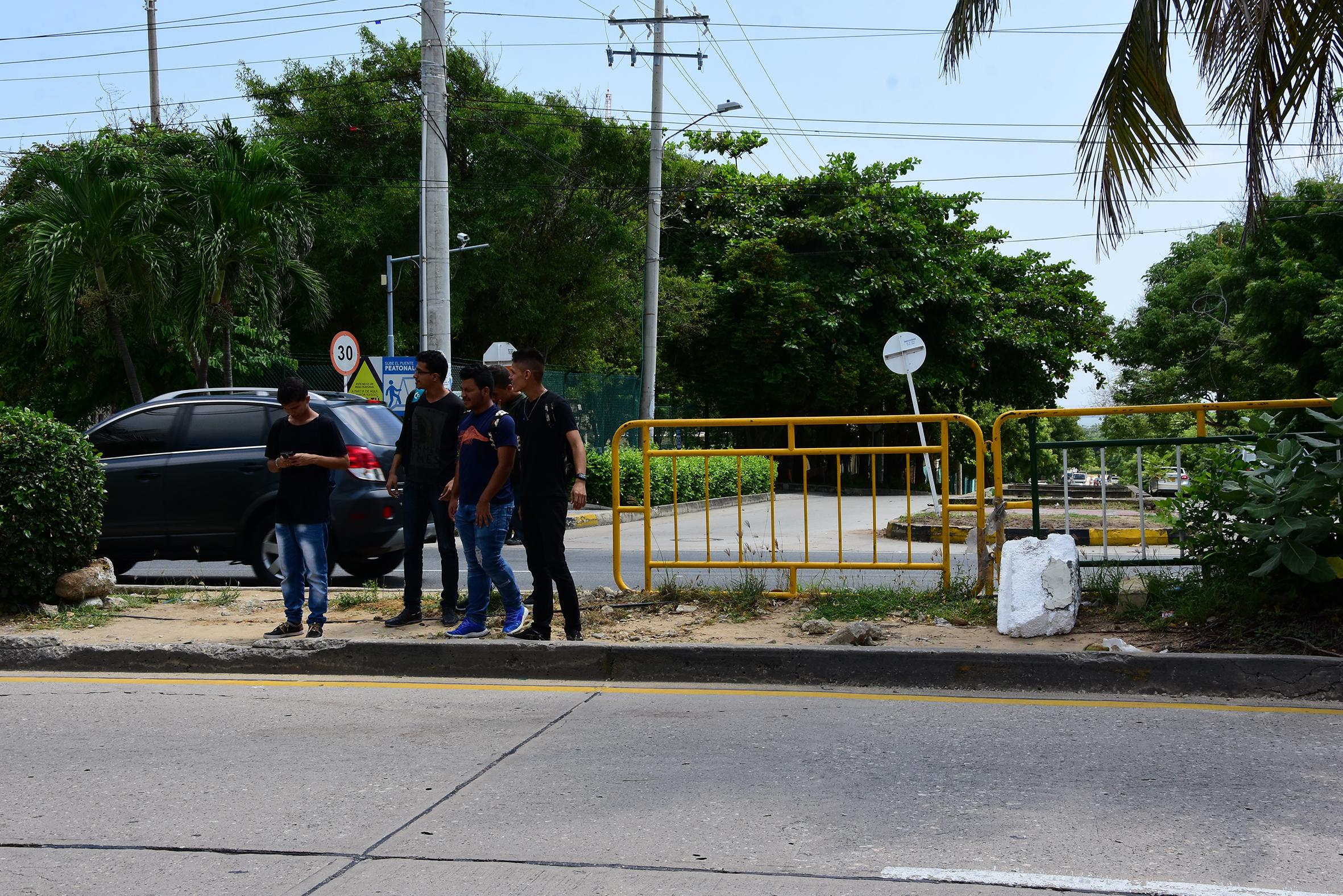 Cuatro estudiantes cruzan la vía por el espacio que dejó el desprendimiento de las vallas a manos de los comerciantes.