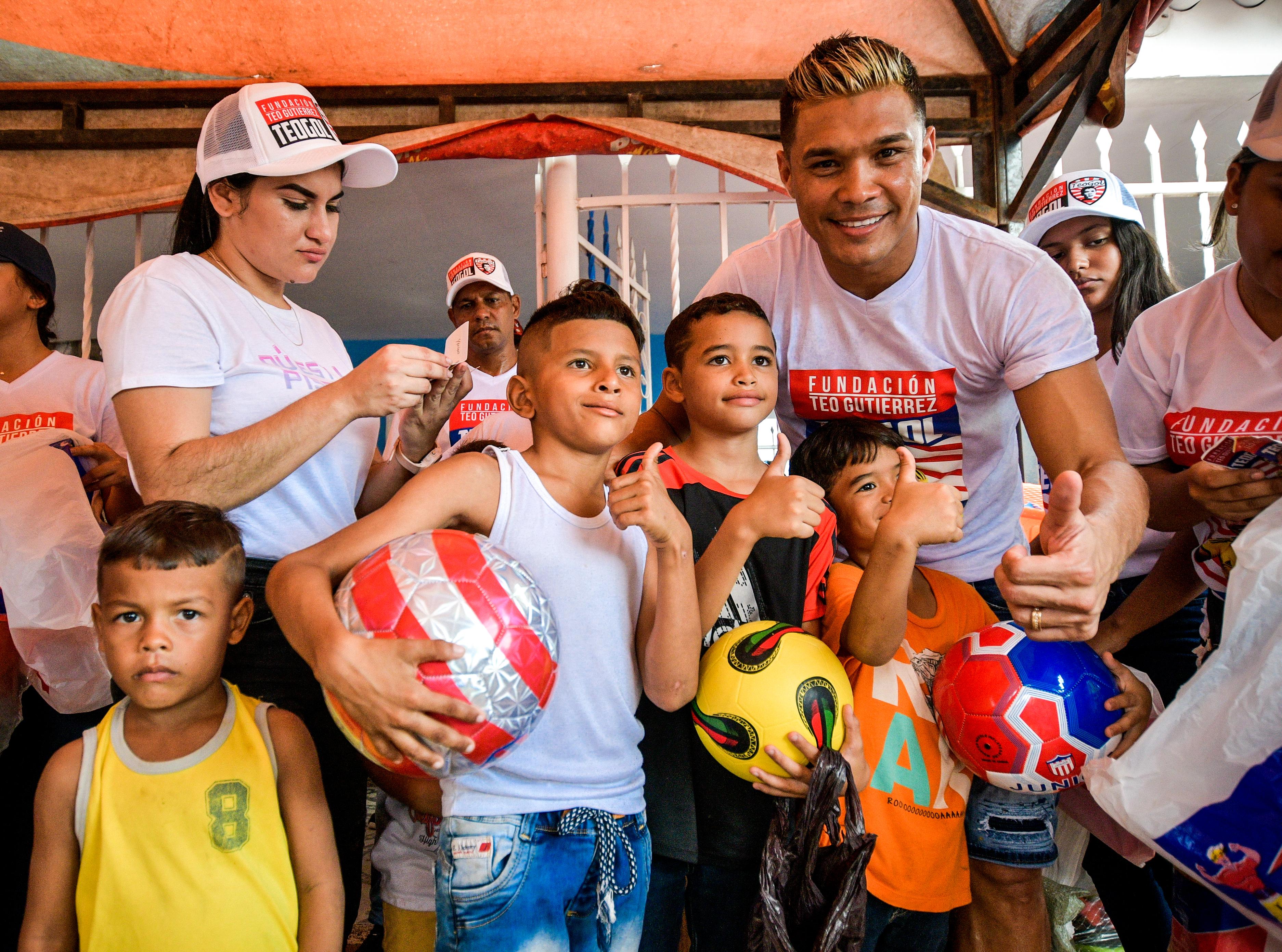El barranquillero Teófilo Gutiérrez posa con algunos de los niños que hicieron parte de la entrega de regalos. 