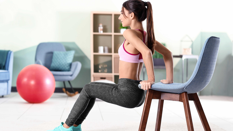 Posición en la que debe realizar los ejercicios de tríceps  en su casa con la ayuda de una silla.