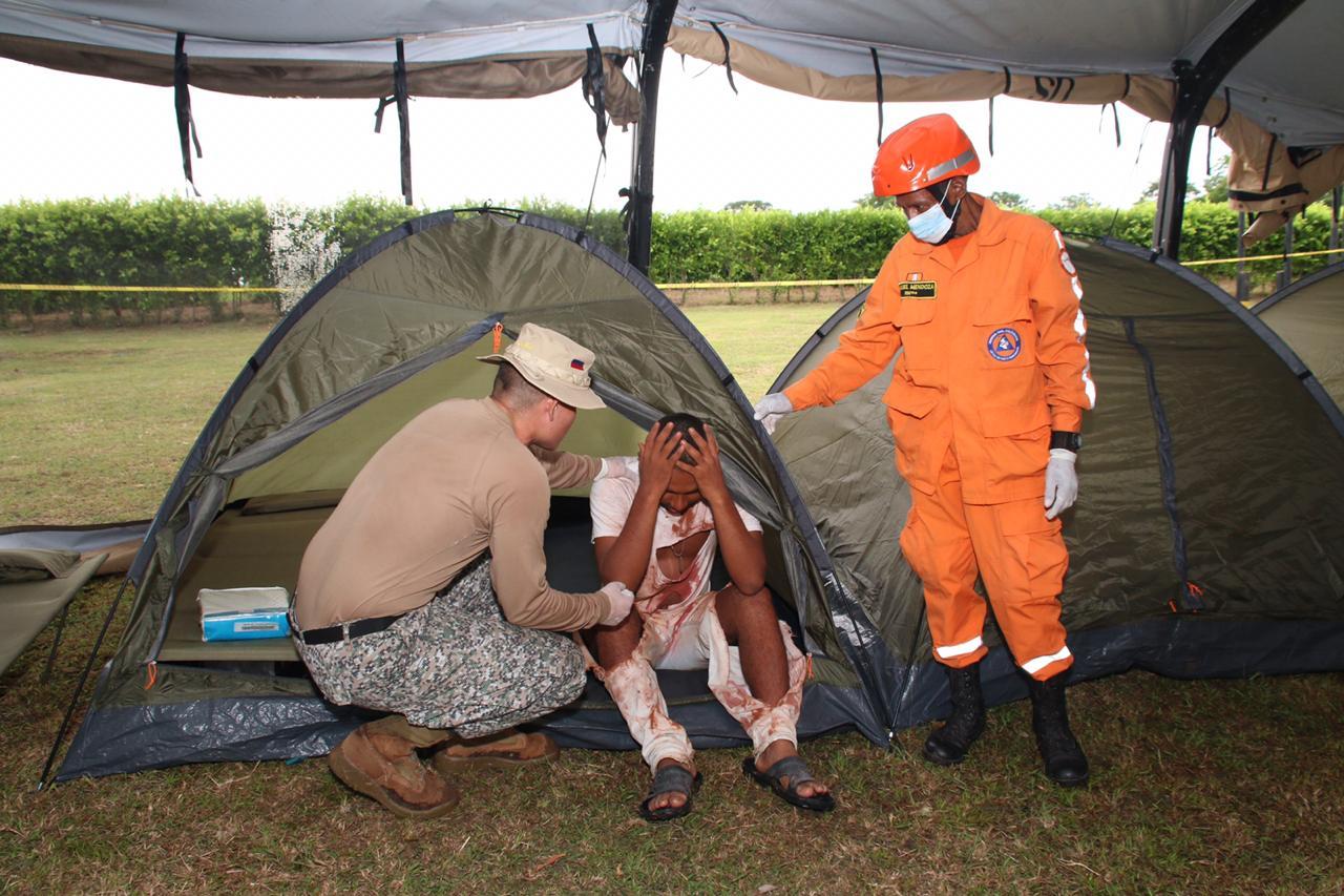 Un soldado y un miembro de las Defensa Civil simulan la atención de un sobreviviente.