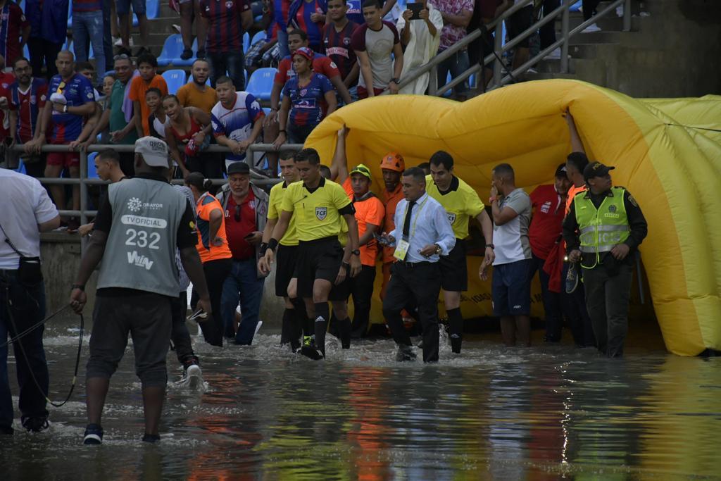 Árbitros y  jugadores caminaron entre el agua.