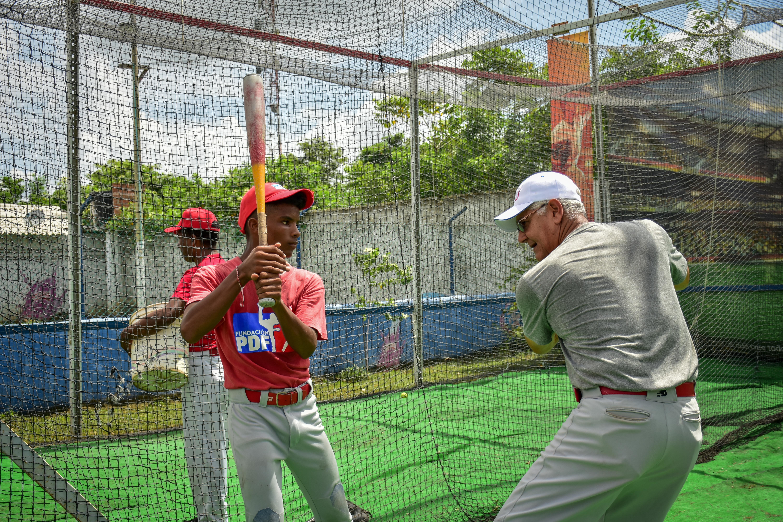 Luis 'el Mello' Sierra enseñándole a un chico técnicas de bateo en la jaula.