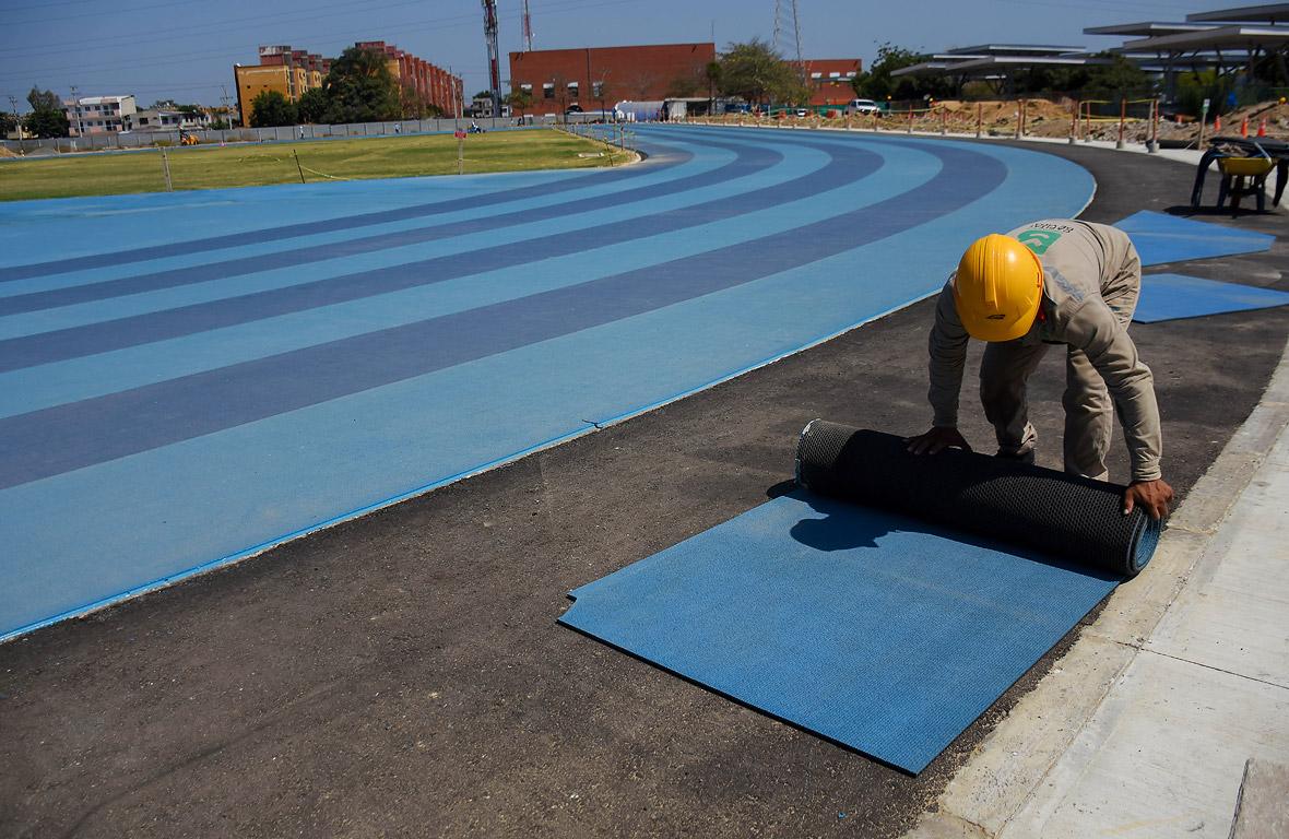 Obreros ultiman detalles del sintético de la pista, que consta de ocho carriles.