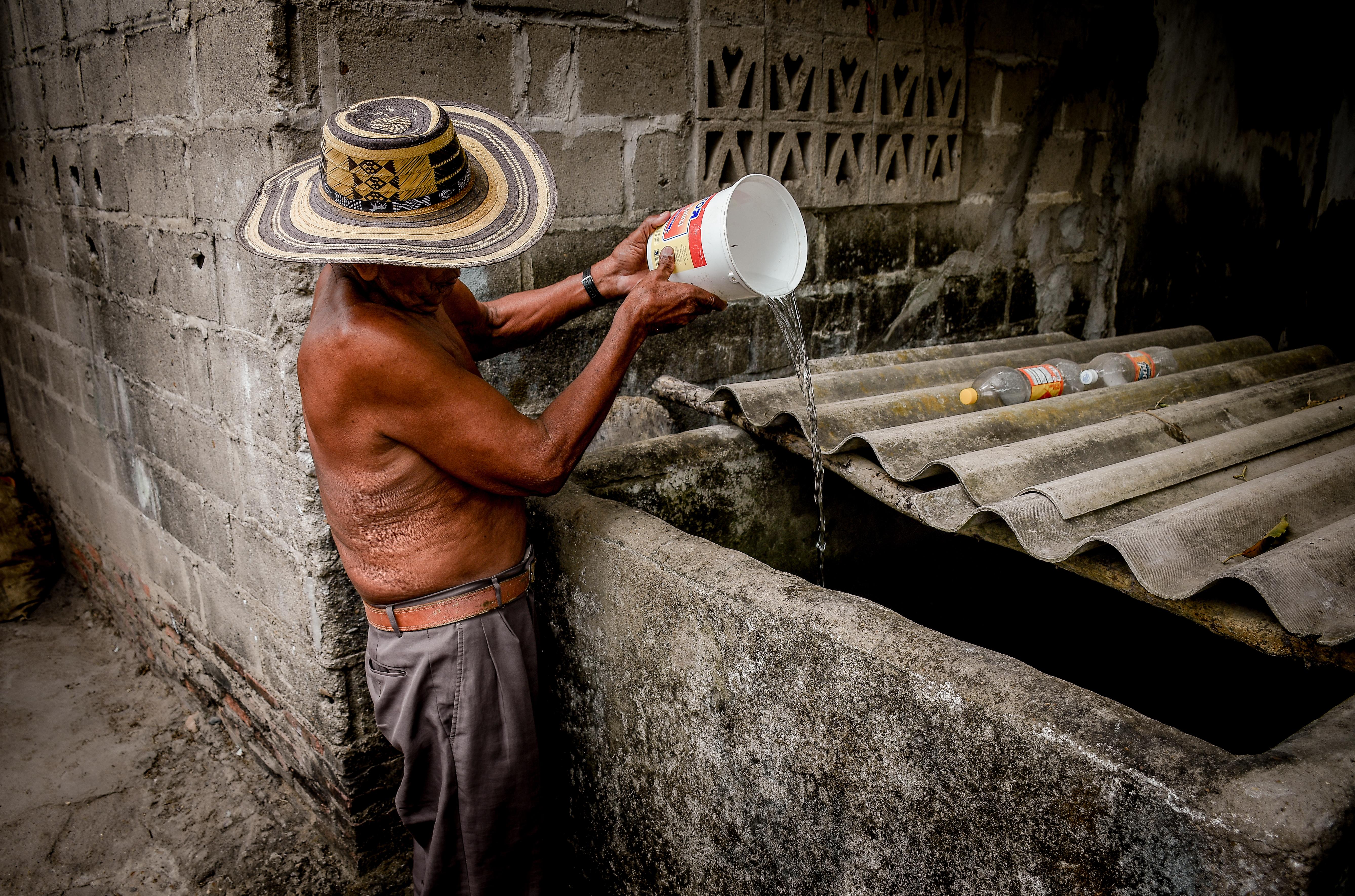 Blas Pérez arroja agua con un balde sobre su alberca.