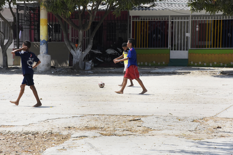 Un grupo de niños juega en la cancha del barrio.