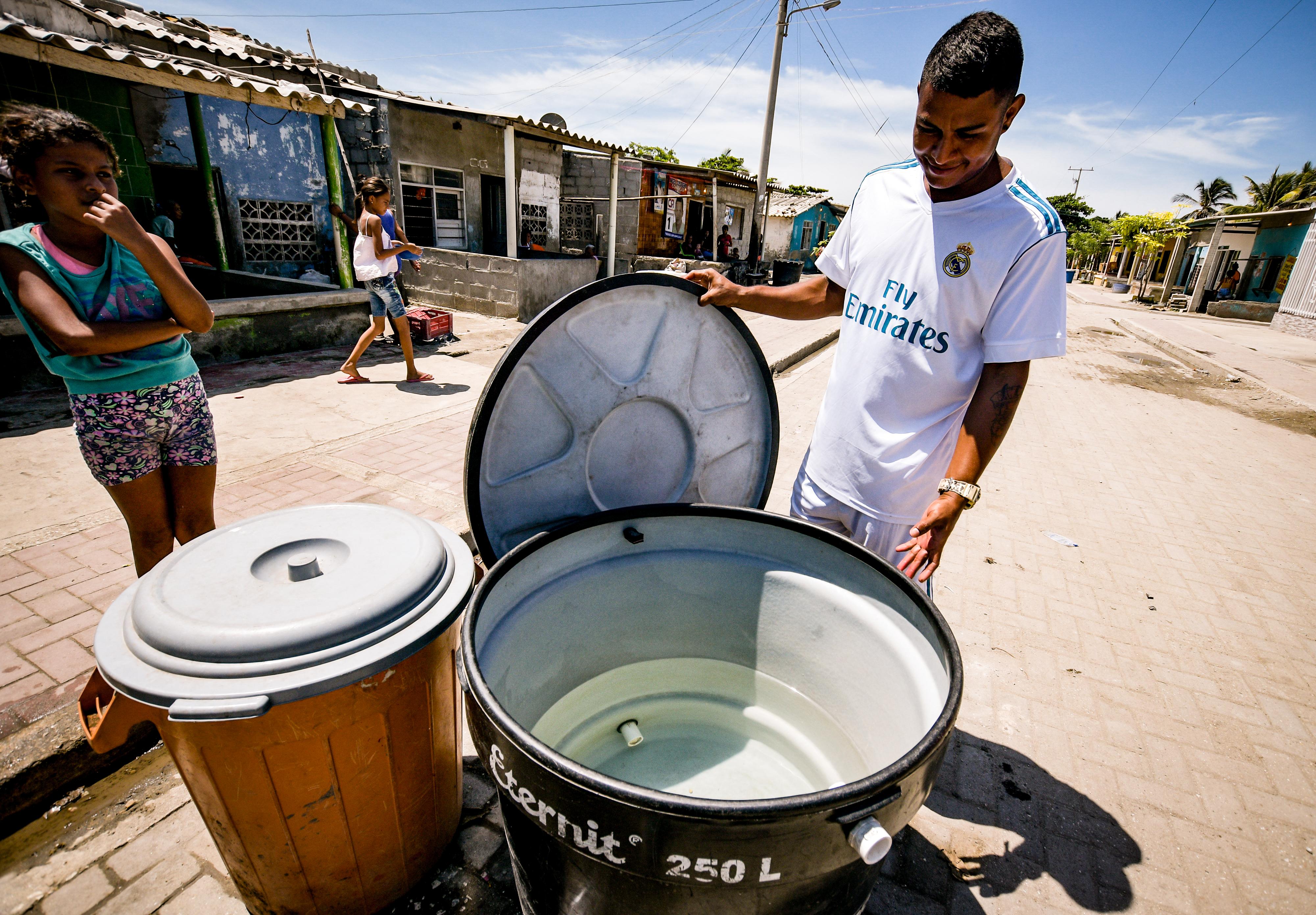 Un habitante del barrio La Gloria revisa el tanque de agua que acaba de comprar.
