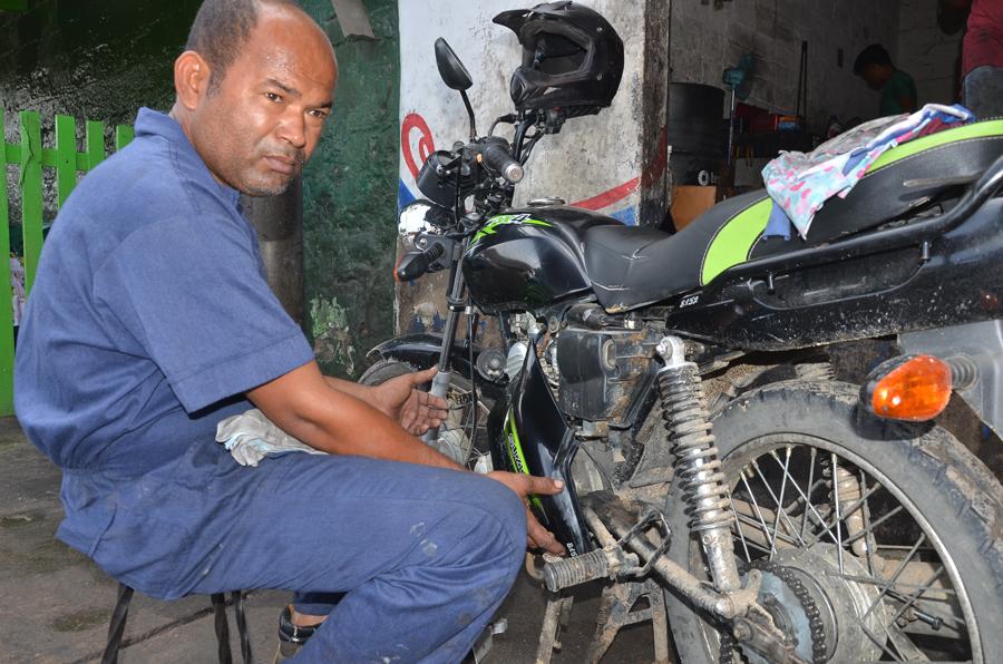 Miguel Iván Palacio habla con EL HERALDO, mientras repara una motocicleta.