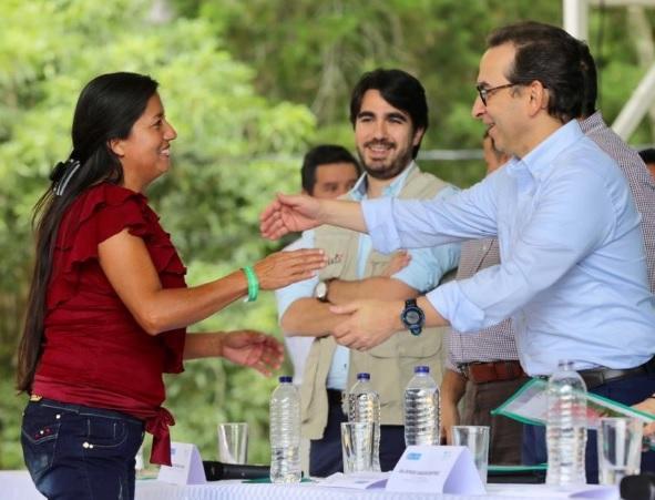 El minagricultura Andrés Valencia entrega un título de propiedad a una habitante de Ovejas.