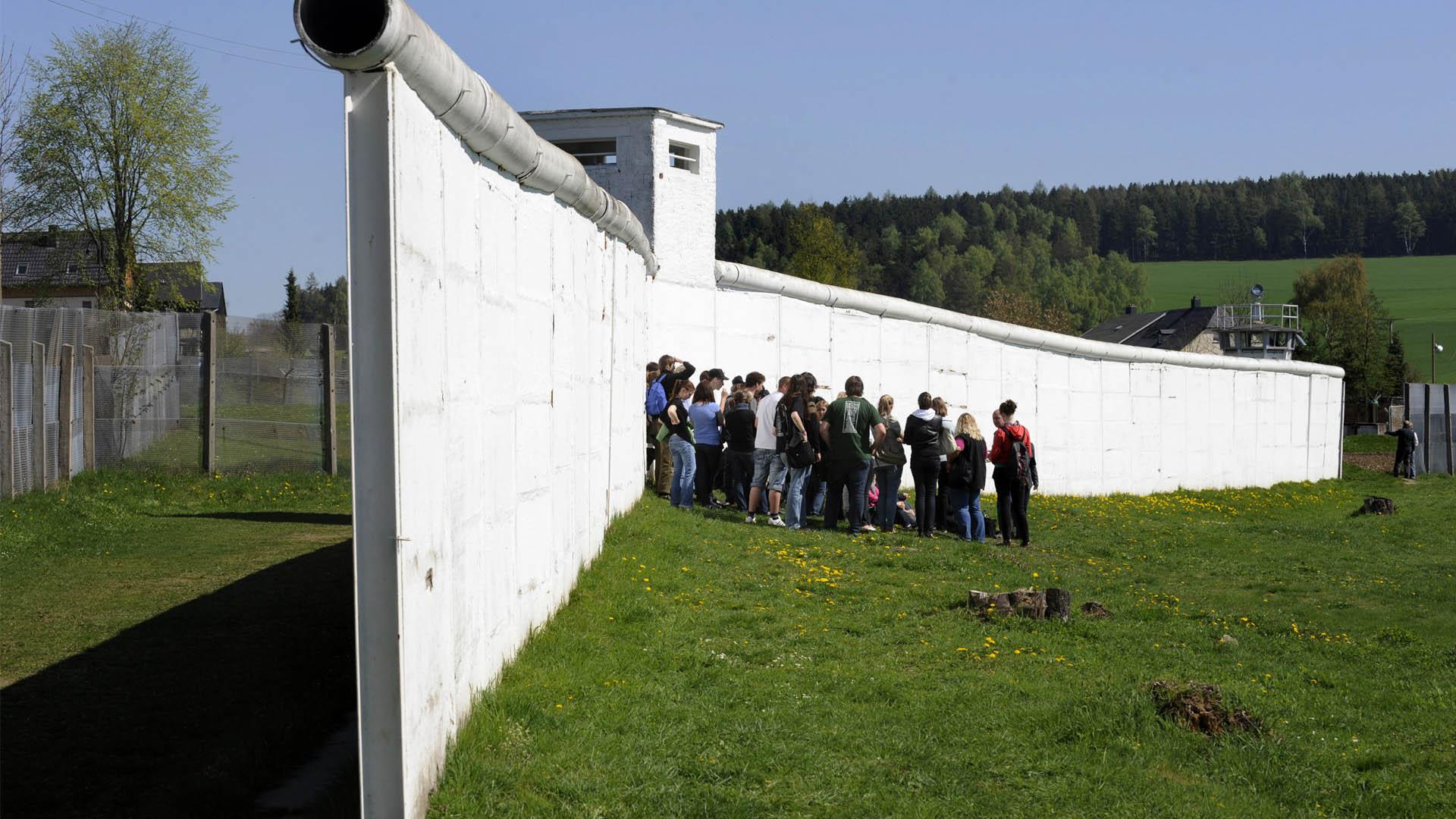 Niños visitan una estructura del muro mantenida como memoria histórica.