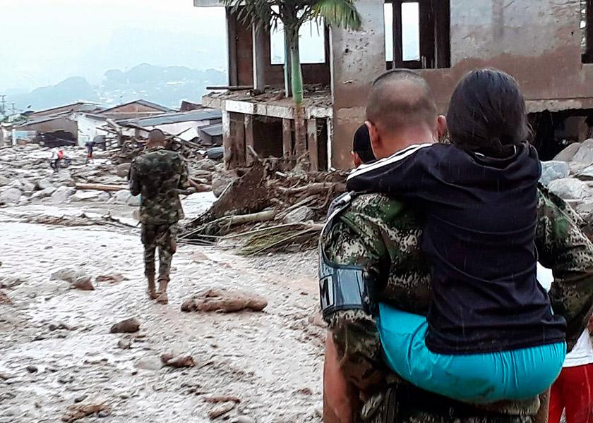 Un soldado carga a una niña damnificada de Mocoa.
