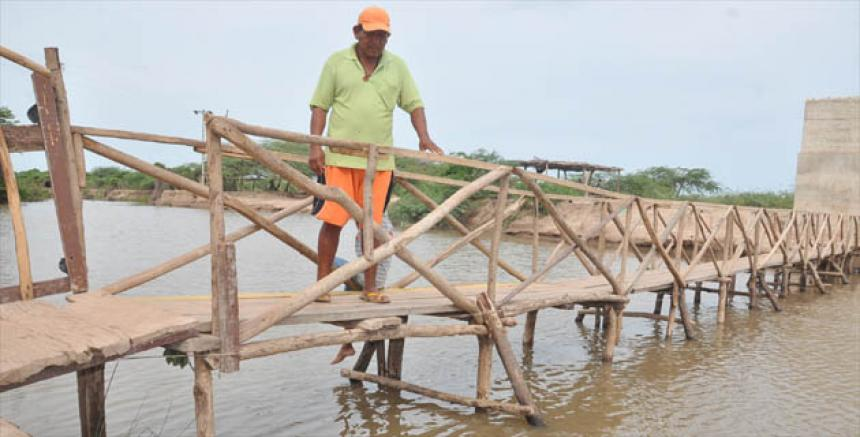 Evelio Pushaina junto al puente que construyó con $50.000 y sirvió por 4 años.