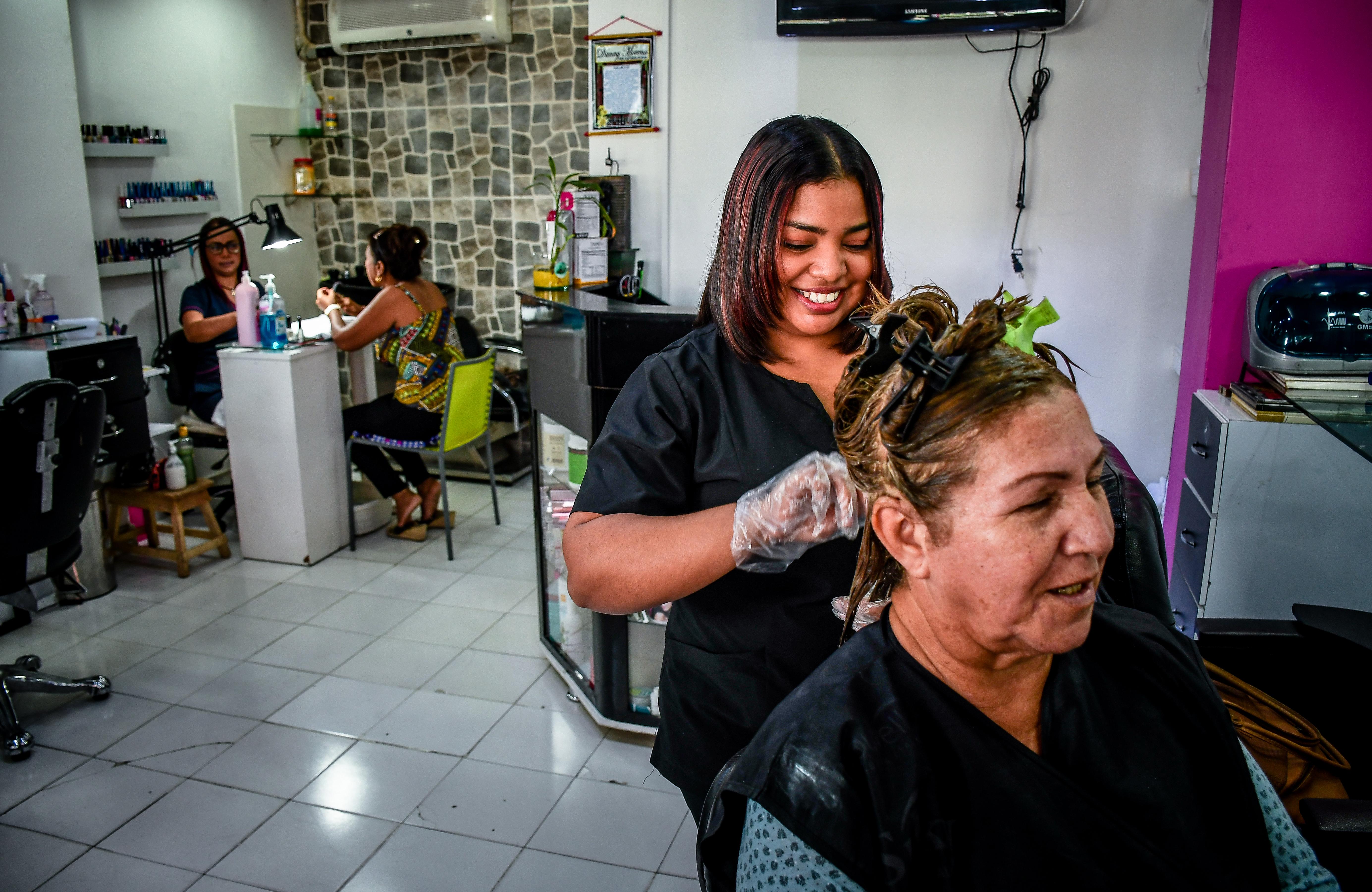 Jesika conversa con su cliente en la peluquería Danny Moreno.