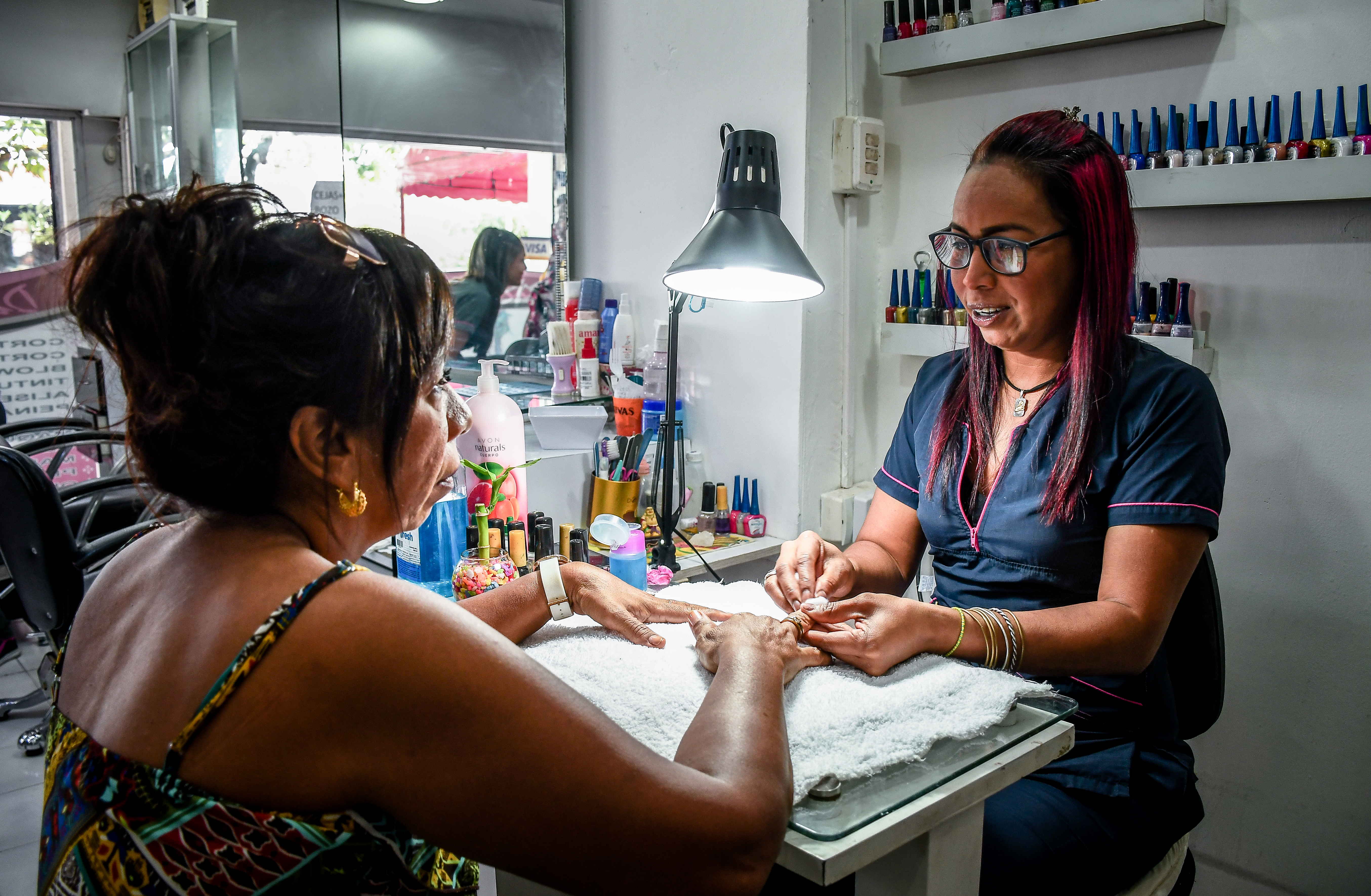 La manicuista Darling Hernández conversa con una de sus clientes.
