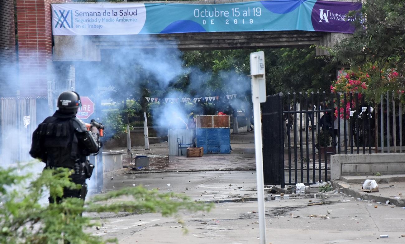 Miembros del Esmad lanzan gases hacia el interior de la universidad para dispersar a los estudiantes.