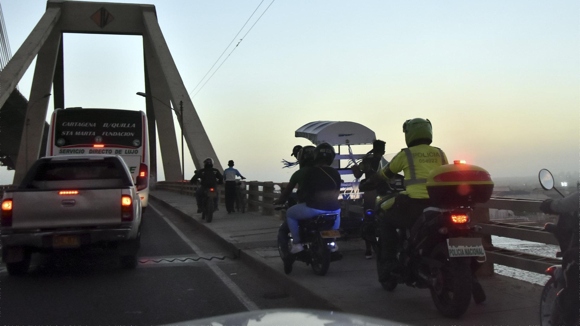 Motorizados cruzan por la zona peatonal del puente.