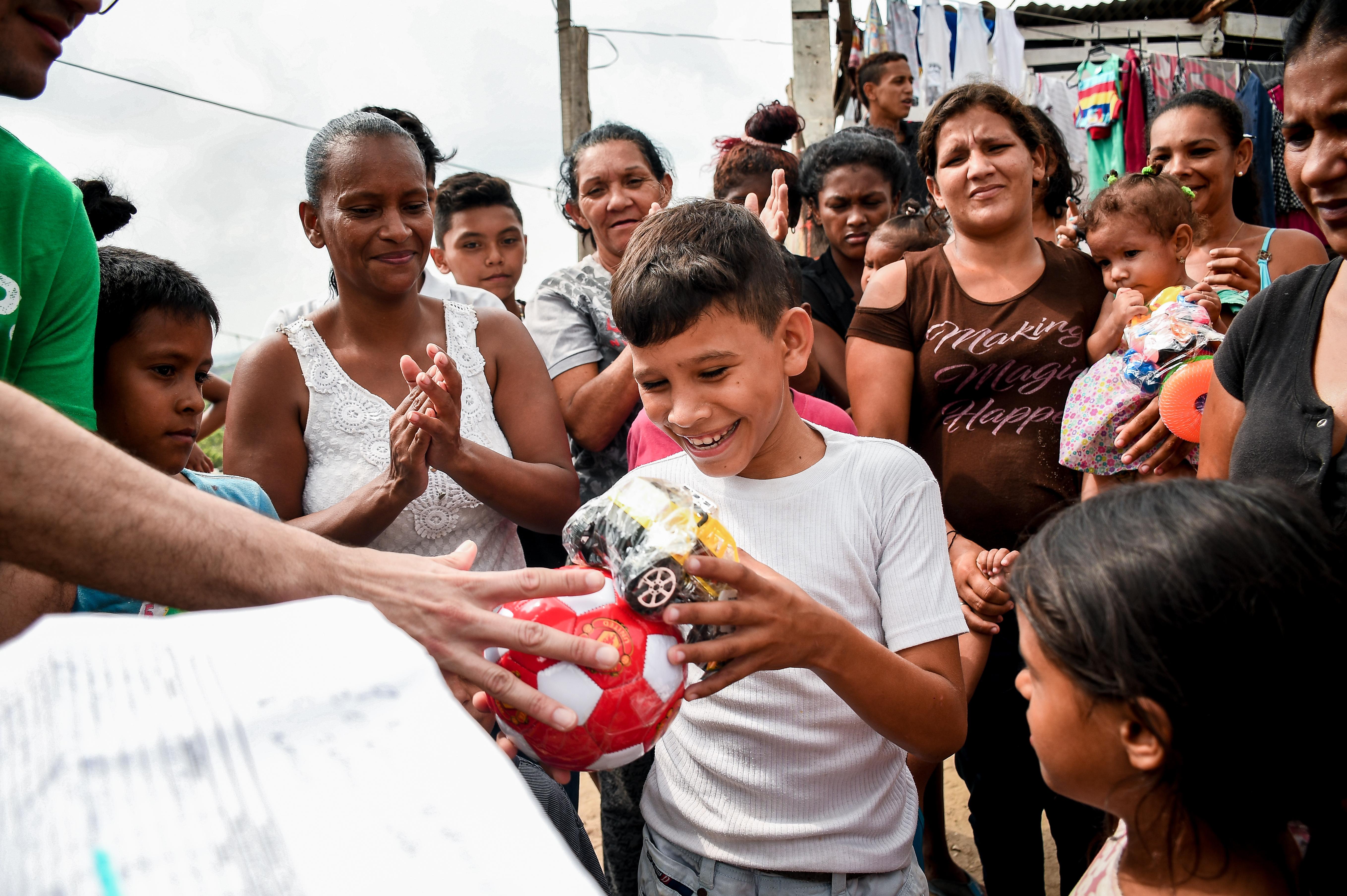 Uno de los niños recibe, con una sonrisa, un balón de fútbol y otros juguetes para la Navidad.