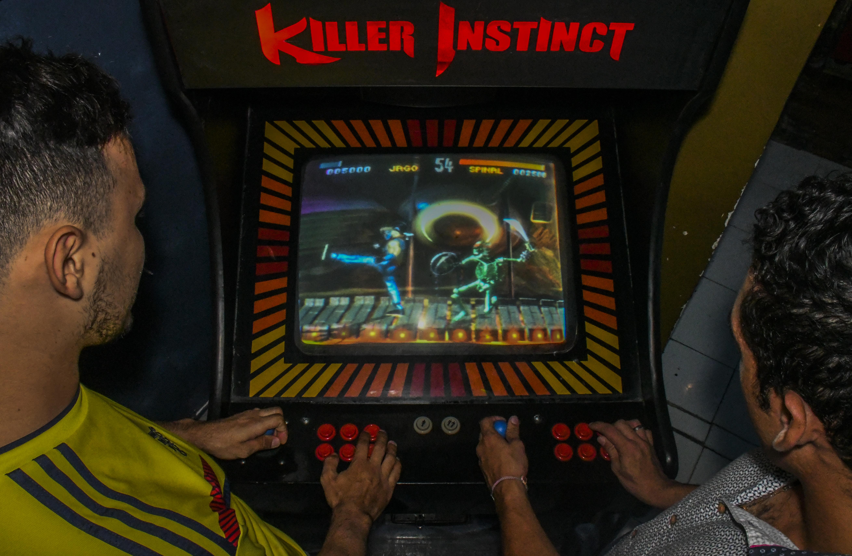 Fanáticos juegan Killer Instinct, un famoso videojuego de lucha en una máquina.