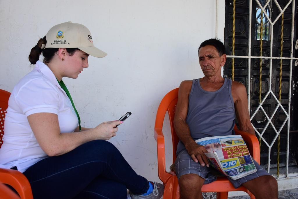 Una funcionaria del Sisbén entrevista a un residente del barrio Santo Domingo.