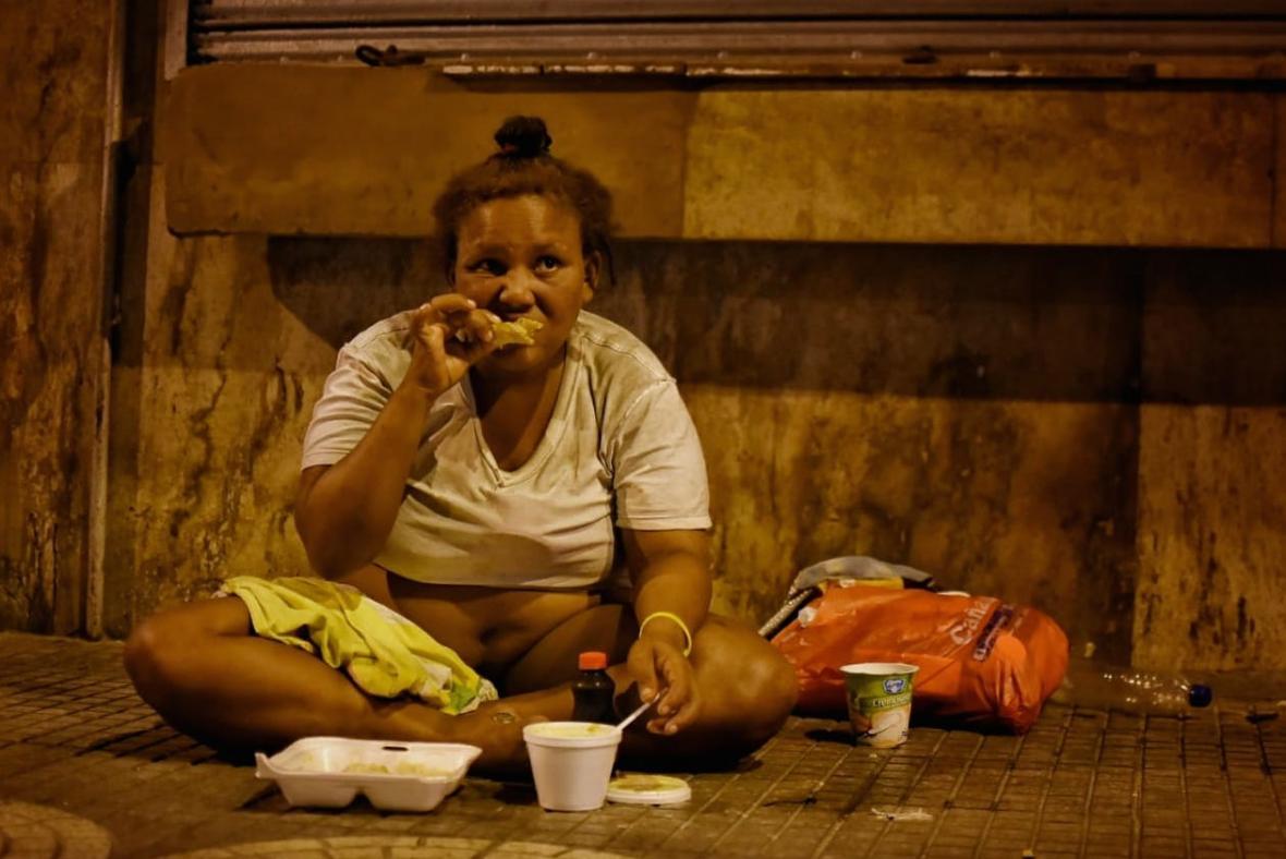 Emily, como se hizo llamar esta mujer habitante de la calle, ingiere alimentos en la vía pública en el Centro de la ciudad.